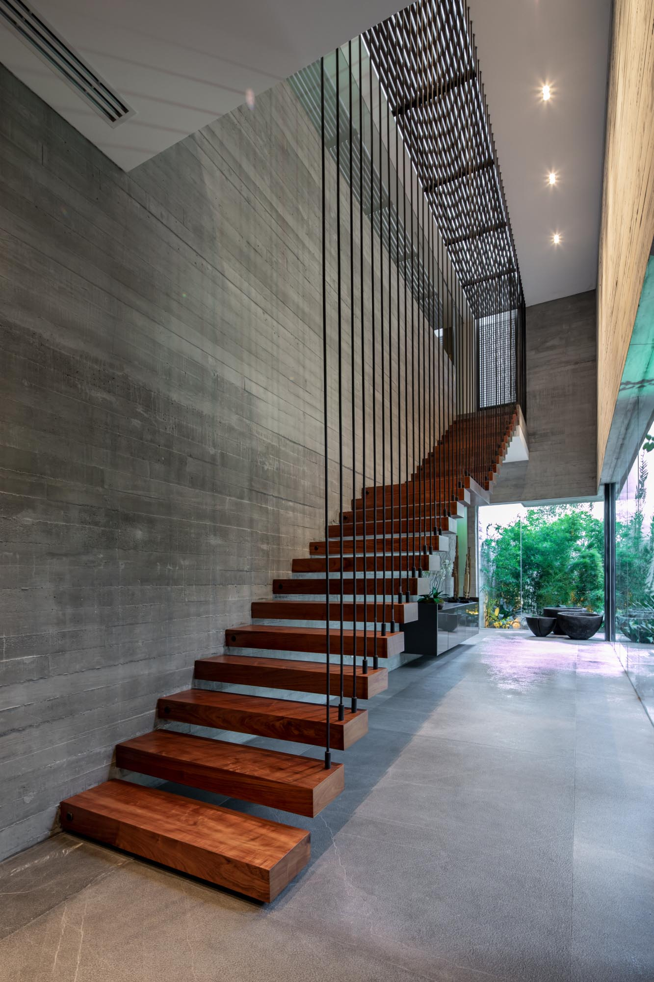 A board-formed concrete wall is visible alongside a wood staircase, which also lights up at night.