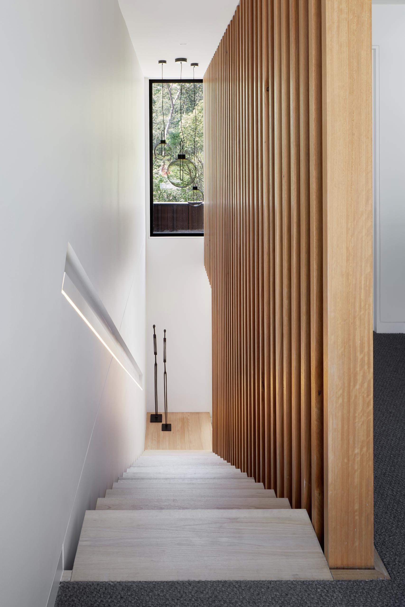 Modern wood stairs with a built-in handrail with lighting.