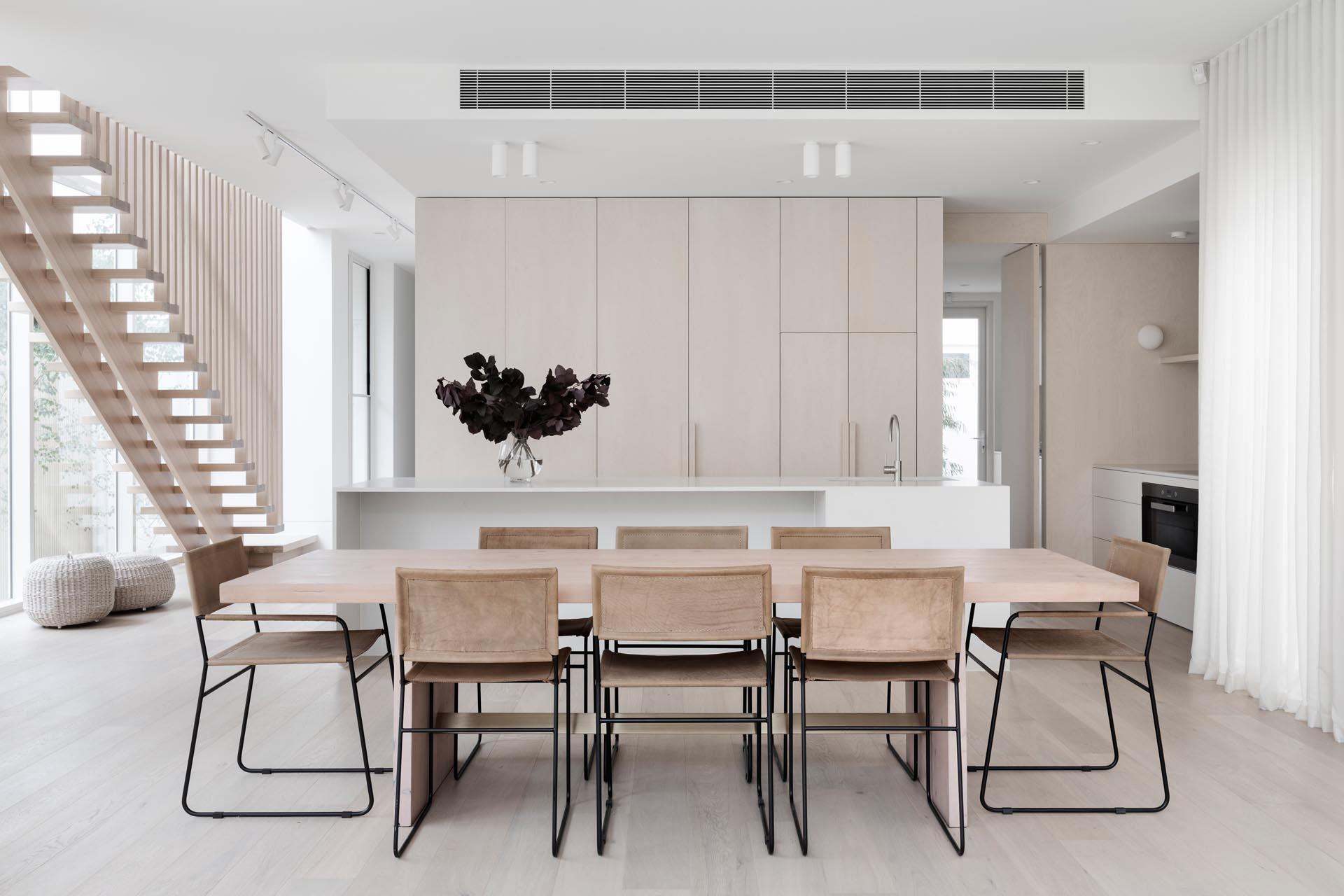 This modern house features a dining room with a light wood table, and a kitchen with minimalist cabinets and a white island.
