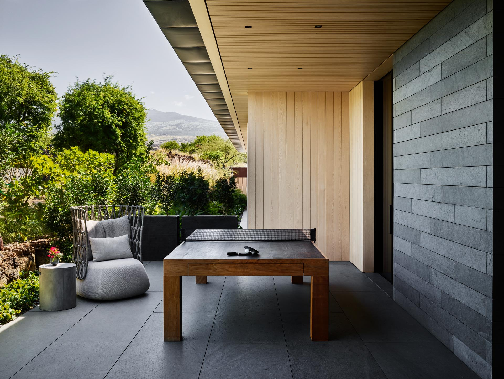 A modern house with an outdoor games area set up with ping pong.