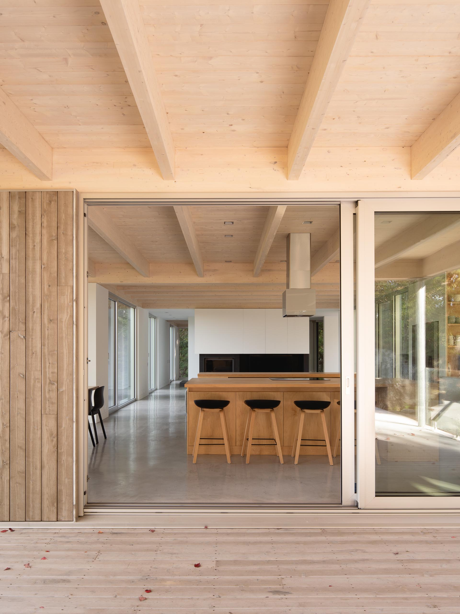 A large sliding door opens the interior spaces of this modern home to a partially covered terrace.