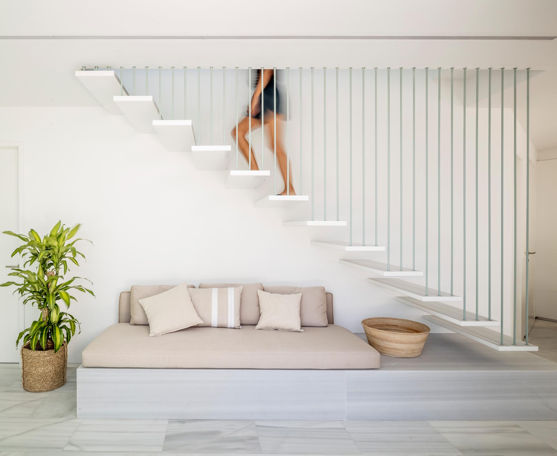 A locally sourced marble and upholstered cushions have been used to create a comfortable seating nook underneath the stairs.