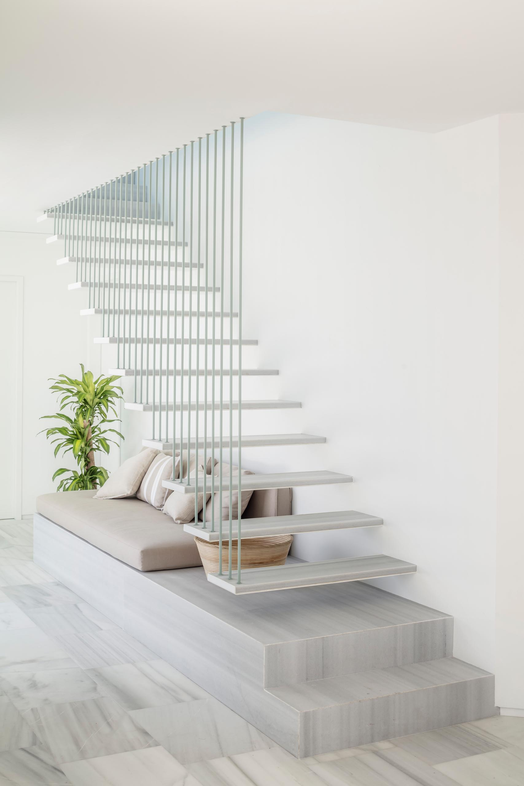 A modern staircase with marble stair treads and a seating nook.