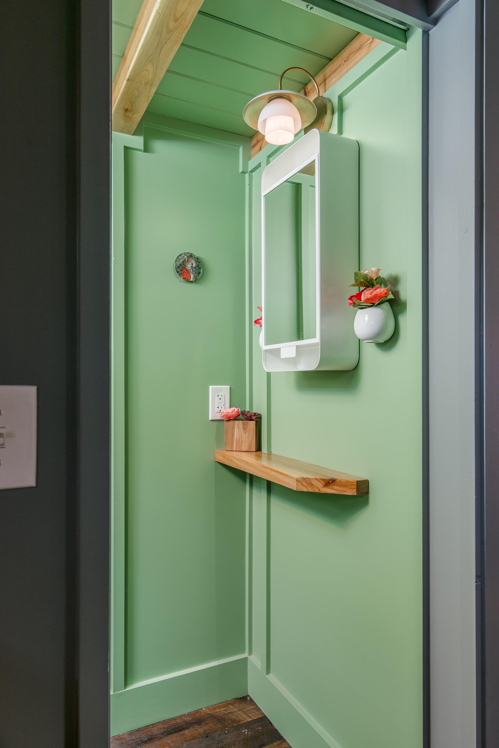 This tiny house bathroom hides behind a sliding pocket door and includes a pastel green finish, a waterless toilet, vanity area, and a shower.