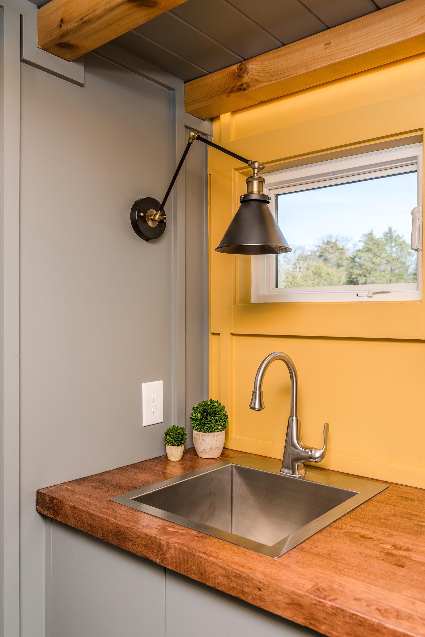 The soft yellow, gray, and wood kitchen of this tiny home includes a stainless steel faucet and matching sink, a dark wood countertop, and floating corner shelves.
