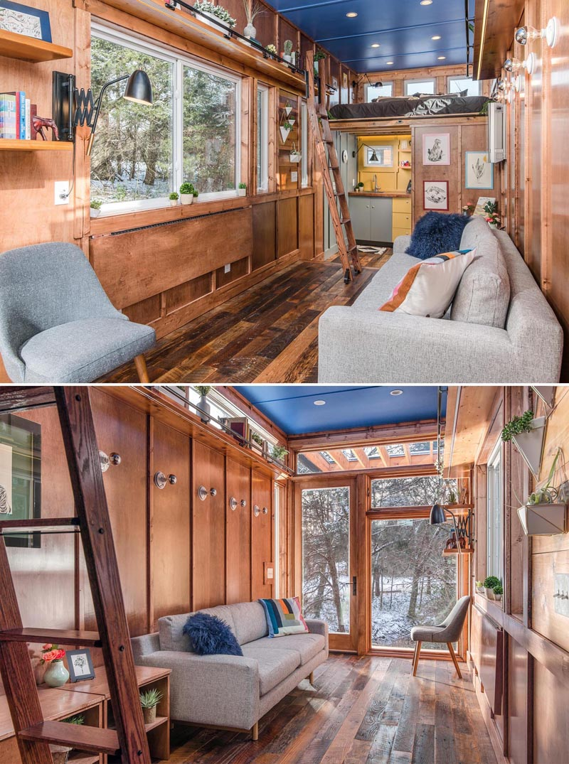 Stepping inside this tiny house, the open space is dedicated to the living room, where you'll find reclaimed hardwood floors and maple siding with maple batten strips.