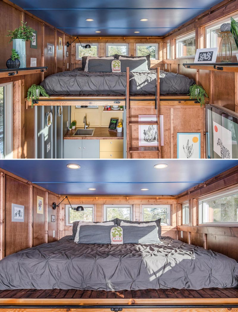 The sleeping loft of this tiny home, which has a king sized bed with a 270-degree view, is located above the kitchen and bathroom and is accessed via a ladder.