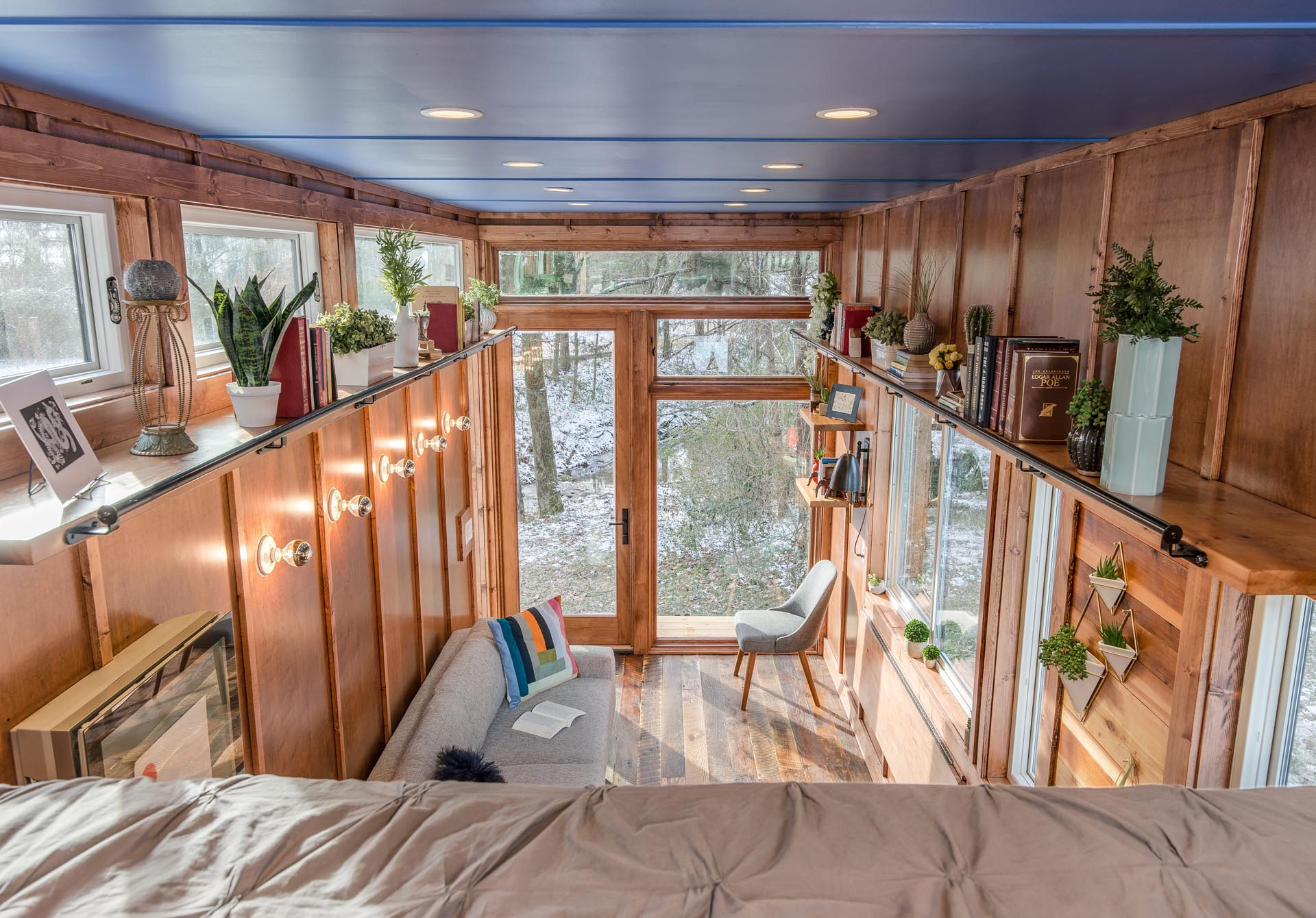 This tiny house has floating cedar library shelves with a rolling ladder.