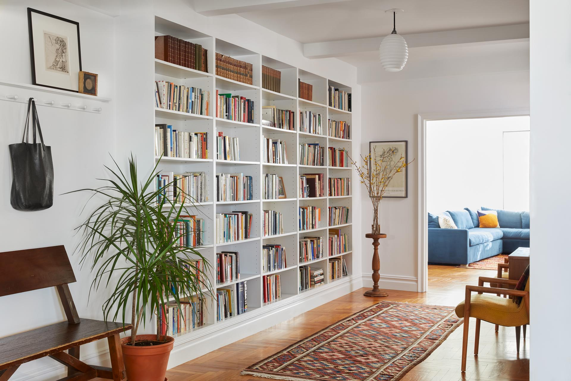 A remodeled entryway with a vintage German Opaline Glass Bauhaus lighting fixture, a Shaker-style hook/shelf system, and a floor-to-ceiling bookcase.
