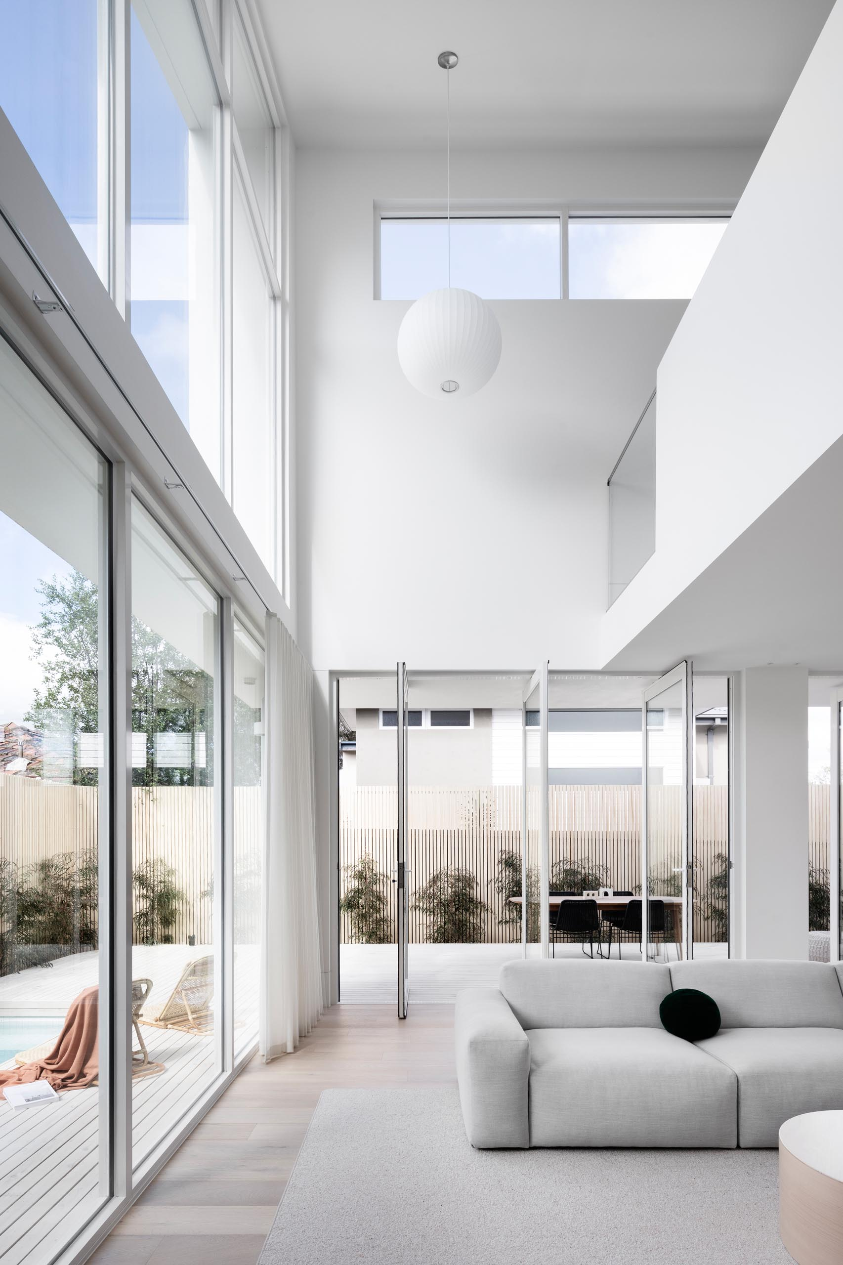 Pivoting sections of glass walls connect the interior spaces with the outdoors of this modern house.