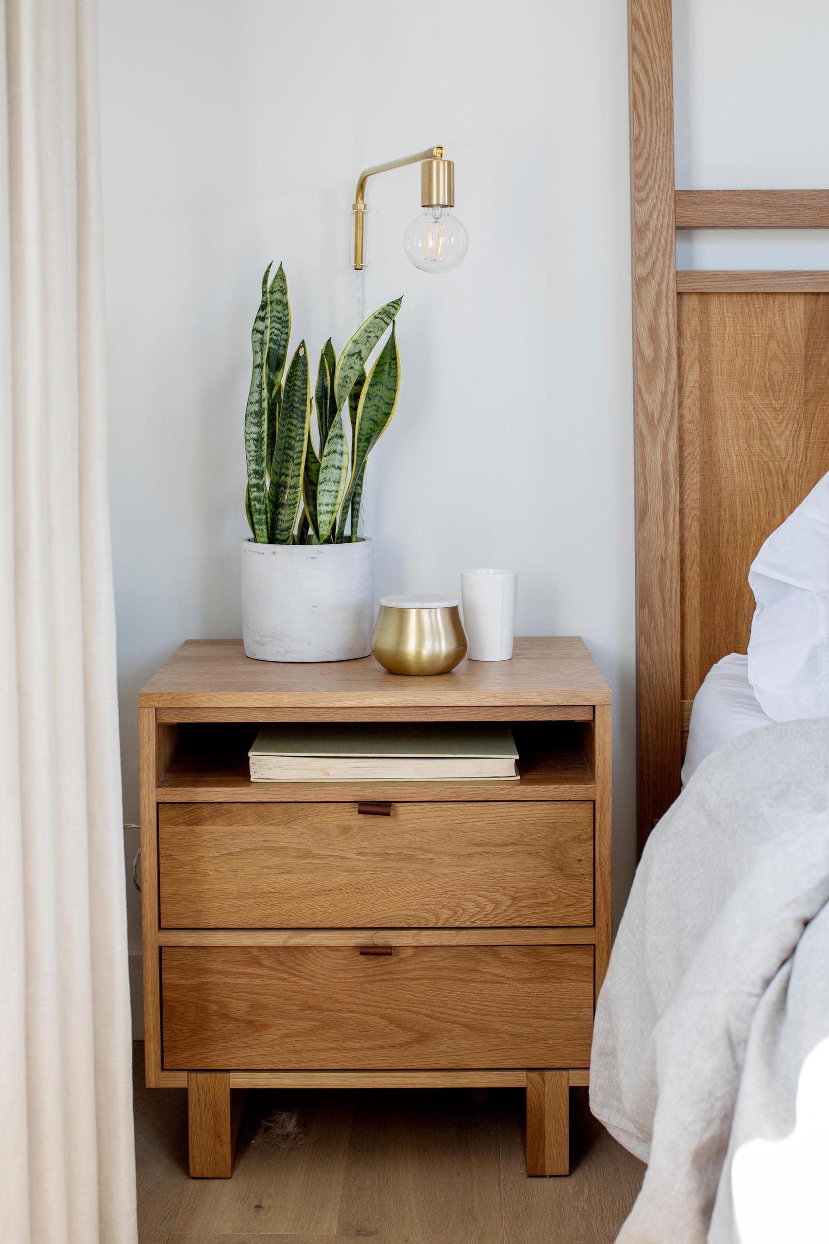 A contemporary wood bedside table with a plant and wall lamp.