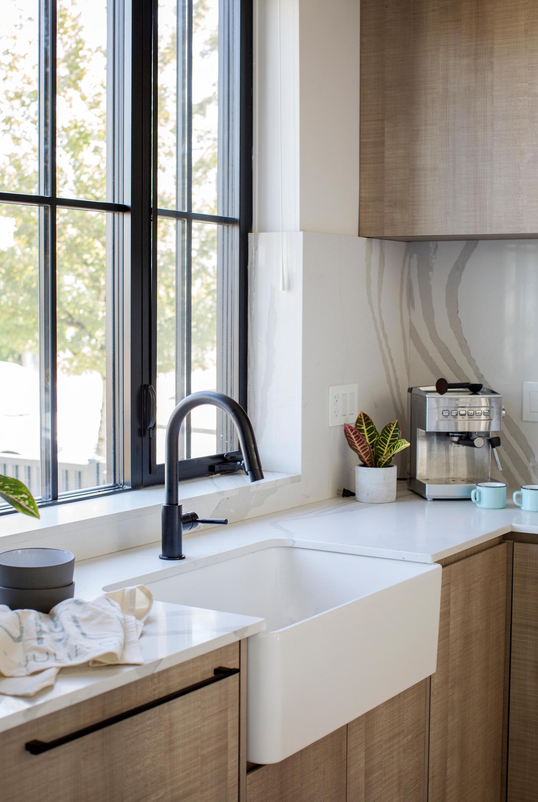 A modern kitchen with an apron front sink, light countertops, and wood cabinets.