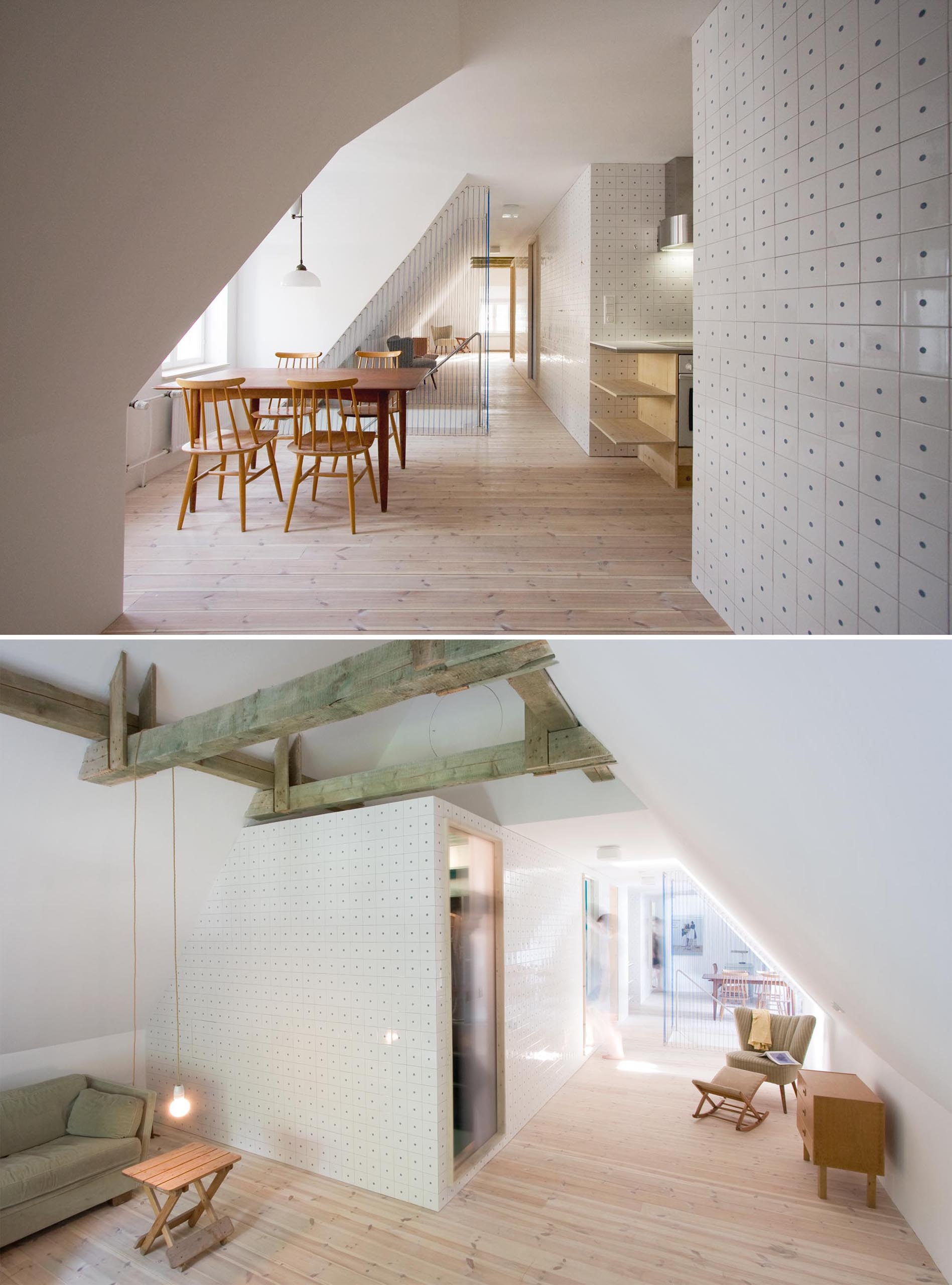 A bright attic with tiled walls, a dining area, a kitchen, and blue rope safety barrier for the stairs.