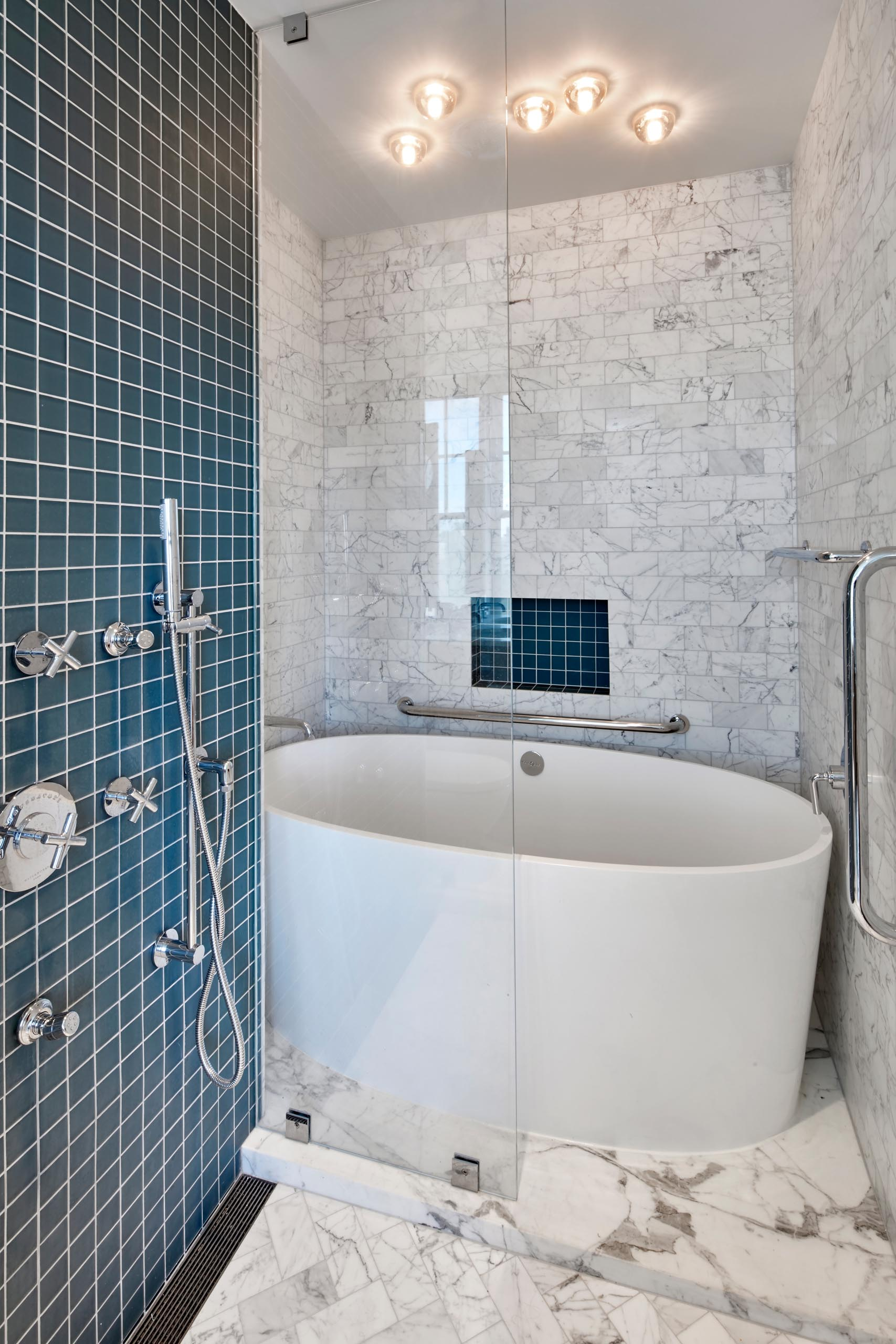 A modern bathroom with white soaking tub, gray marble subway tiles, and shower and a shelving niche lined with square turquoise tiles.