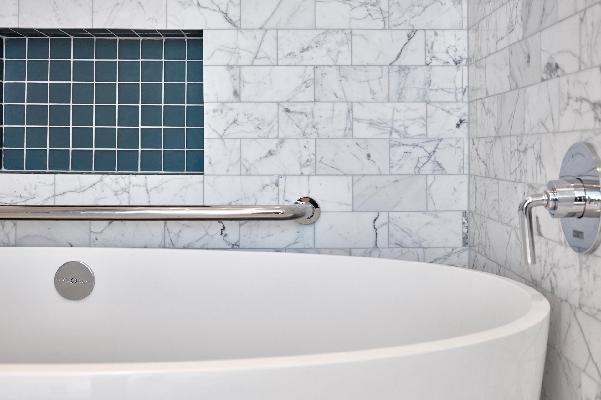 A modern bathroom with white soaking tub, gray marble subway tiles, and a shelving niche lined with square turquoise tiles.