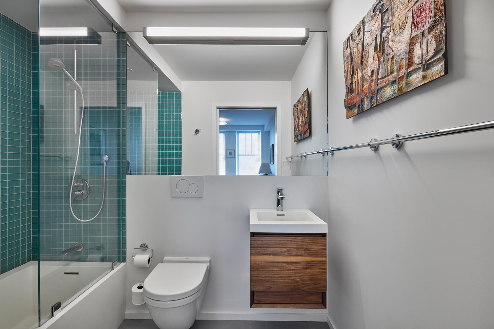 A modern bathroom with bright white walls, a simple wood vanity with white sink, and a shower/bath combo with square turquoise tiles on the walls.