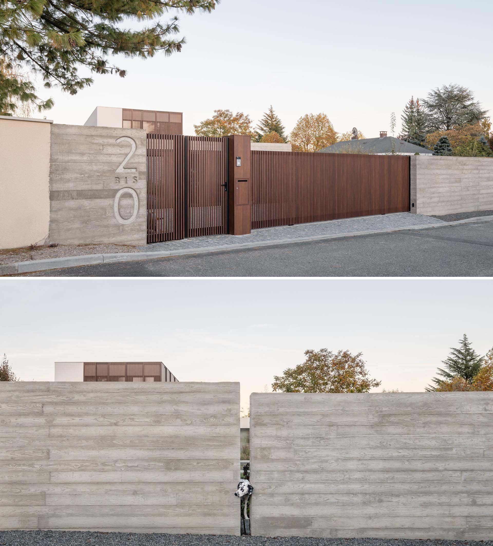 A modern concrete front wall with wood gate and driveway access.