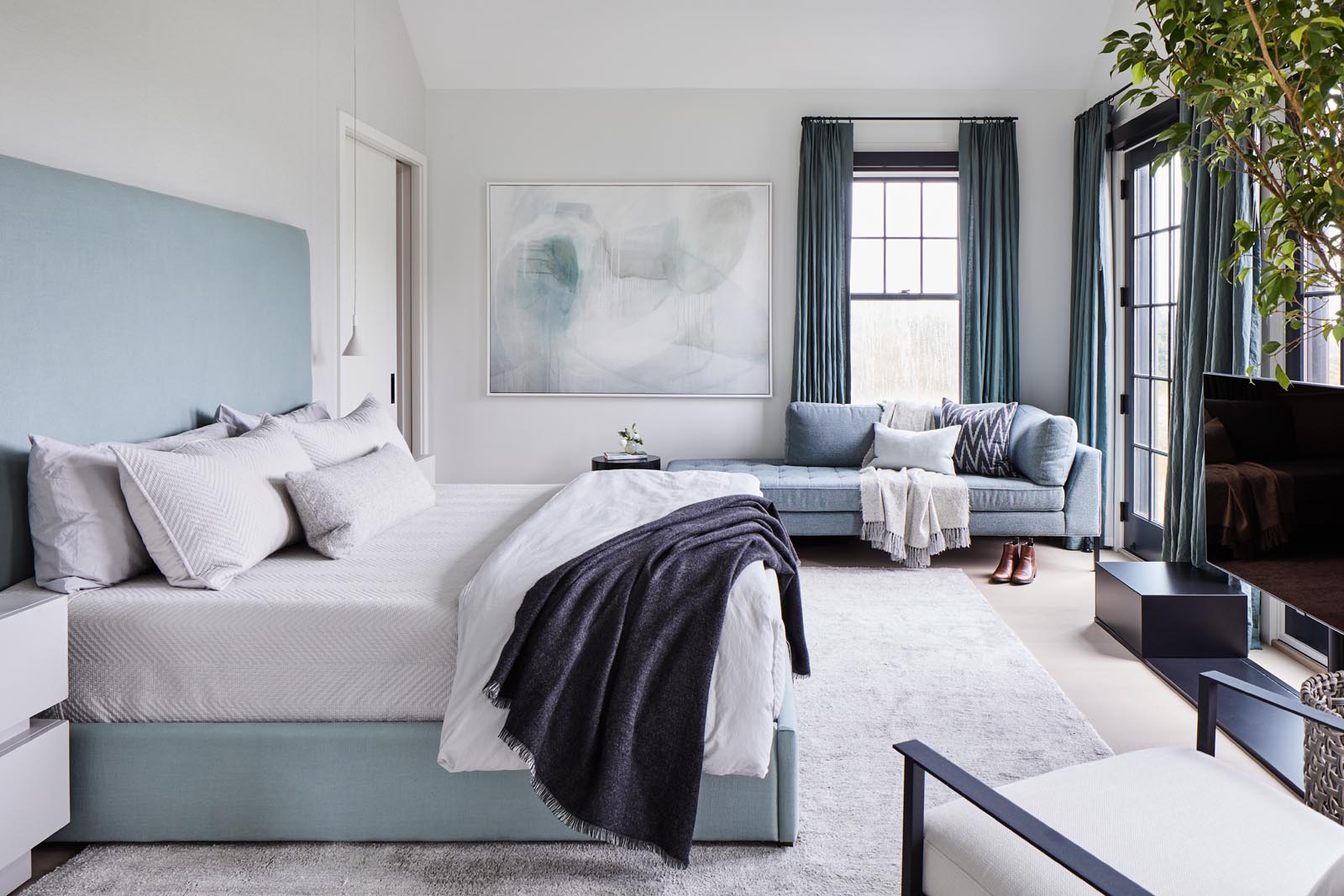 A sun-soaked master bedroom was designed with a calming light blue color palate inspired by the home's natural surroundings.