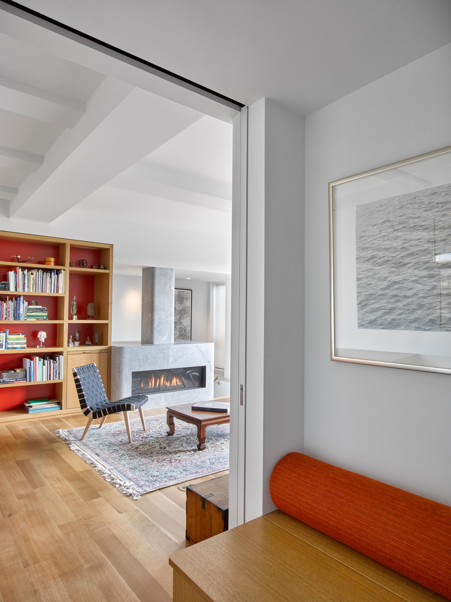 A modern living room with custom shelving and a grey stone fireplace surround.