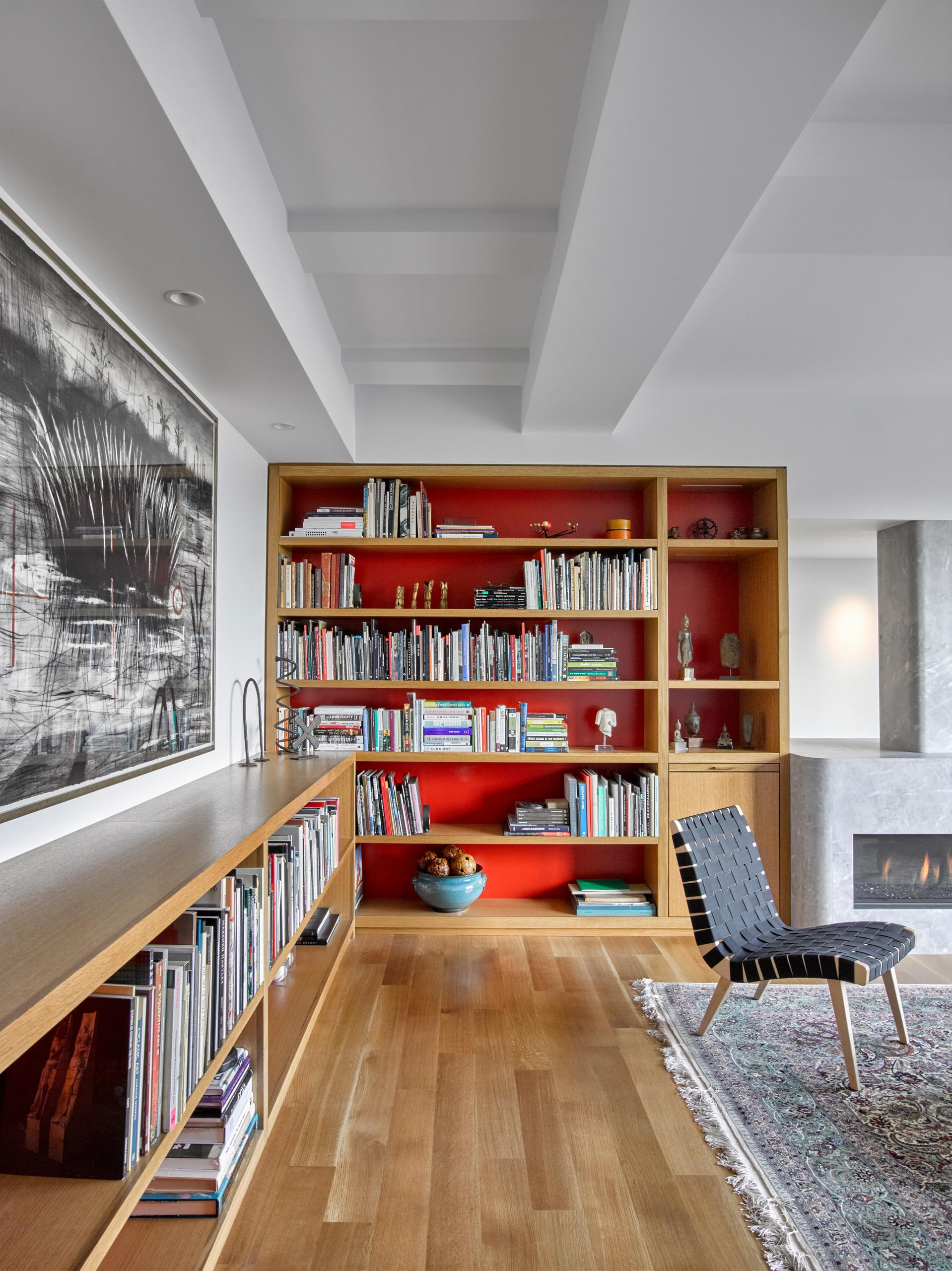 A custom wood shelving unit runs along the wall and transitions into a bookshelf with LED lighting.