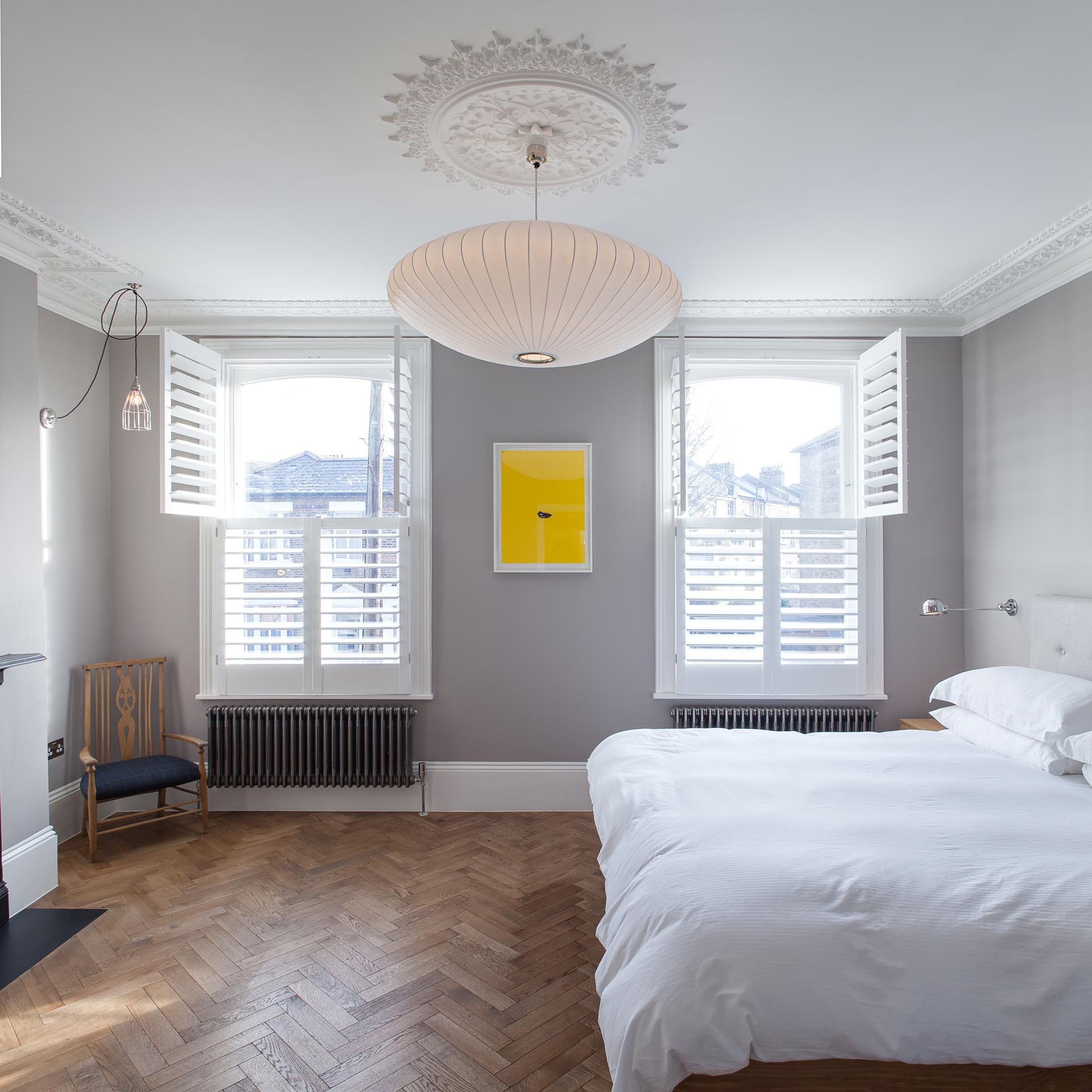 A contemporary bedroom with gray walls accented by white trim and window shutters.