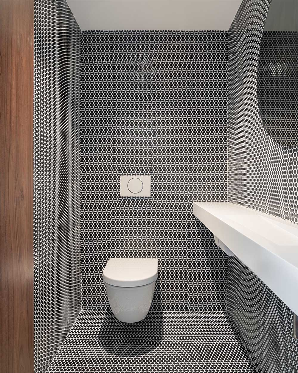A modern powder room that has black penny tiles with white grout that cover the walls and floor.