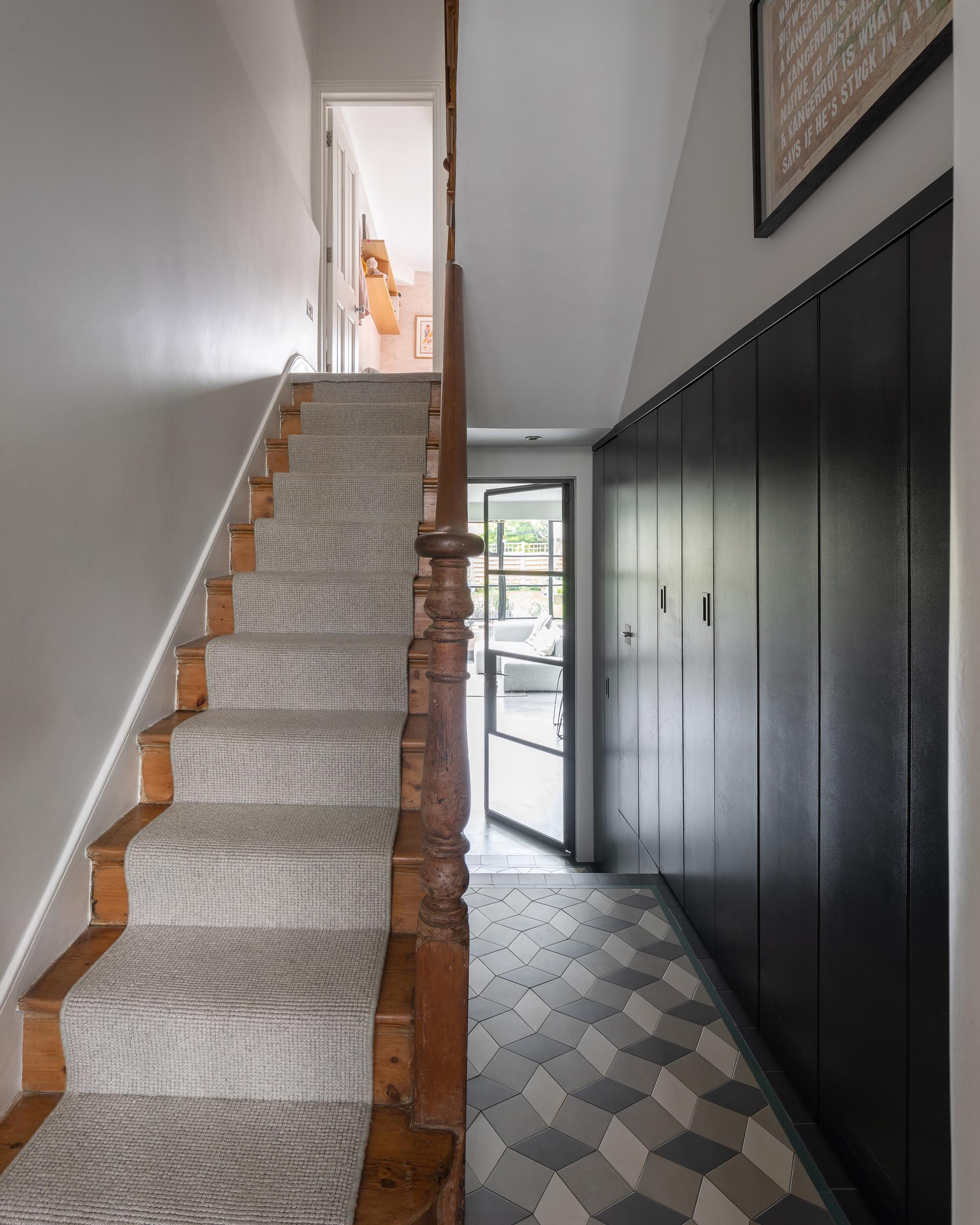 A hallway and staircase connect the original home to a new addition.