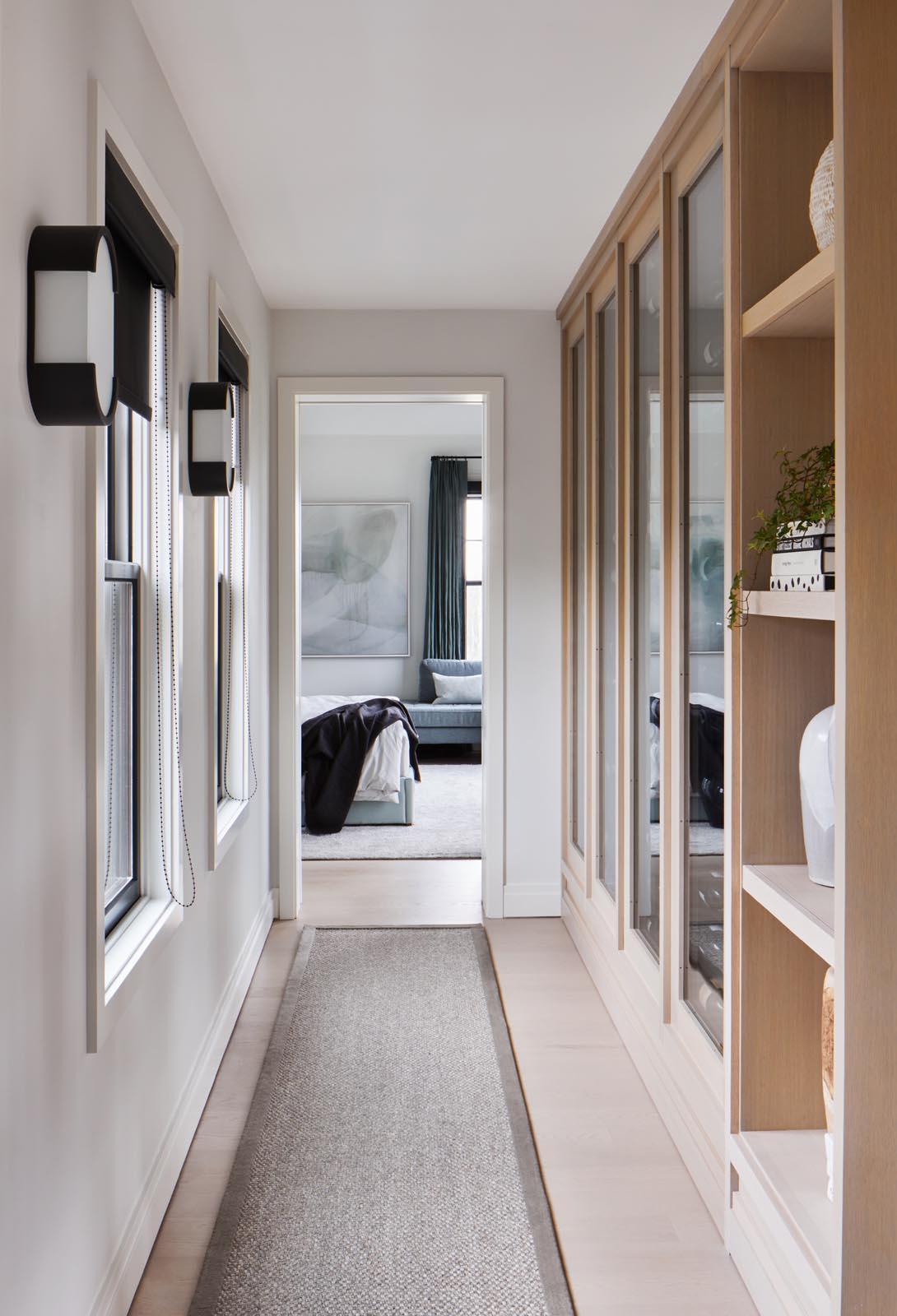 A hallway lined with wood shelving and cabinets leads to the master bedroom.