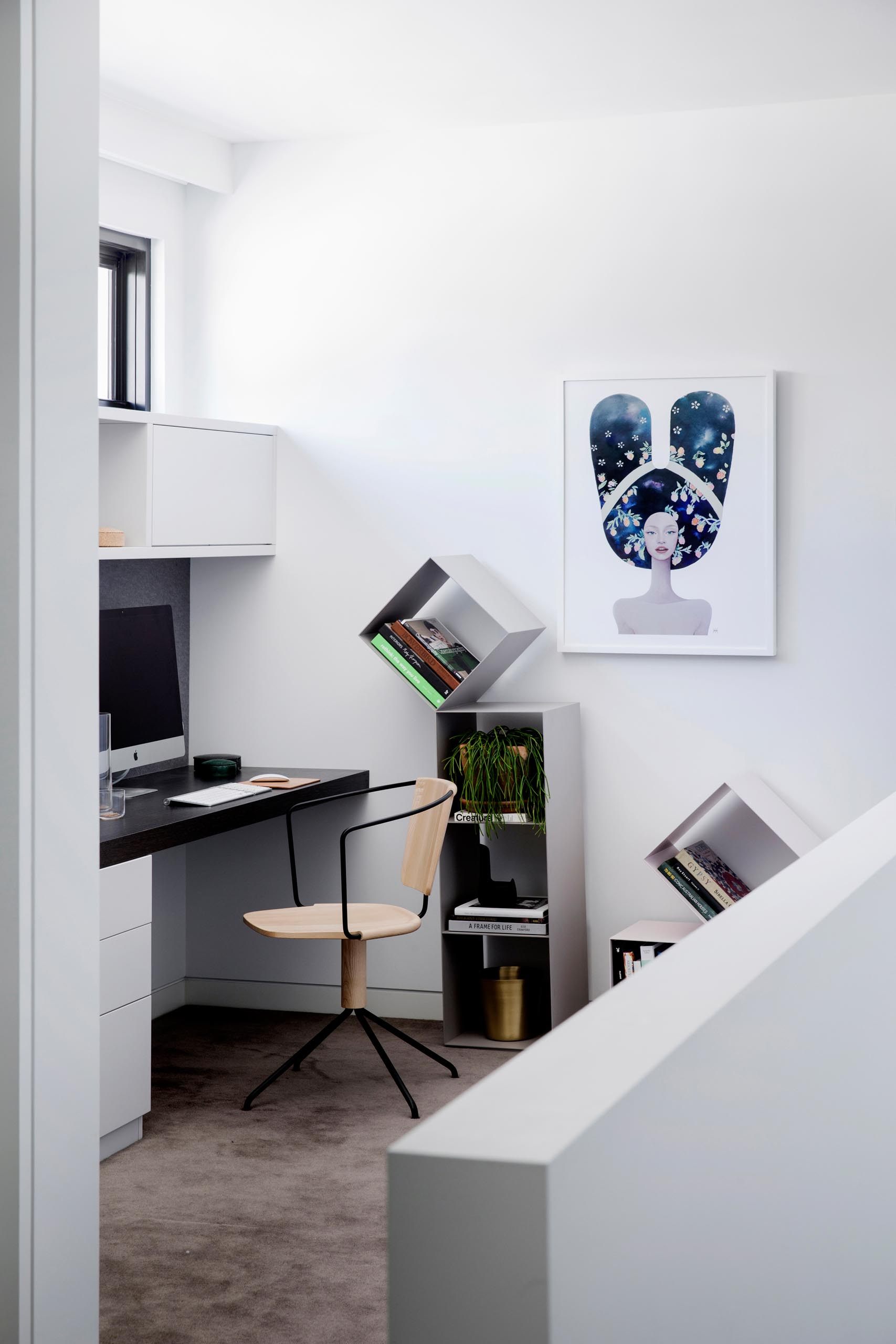 A home office nook with a custom desk and cabinets, and freestanding bookshelves.