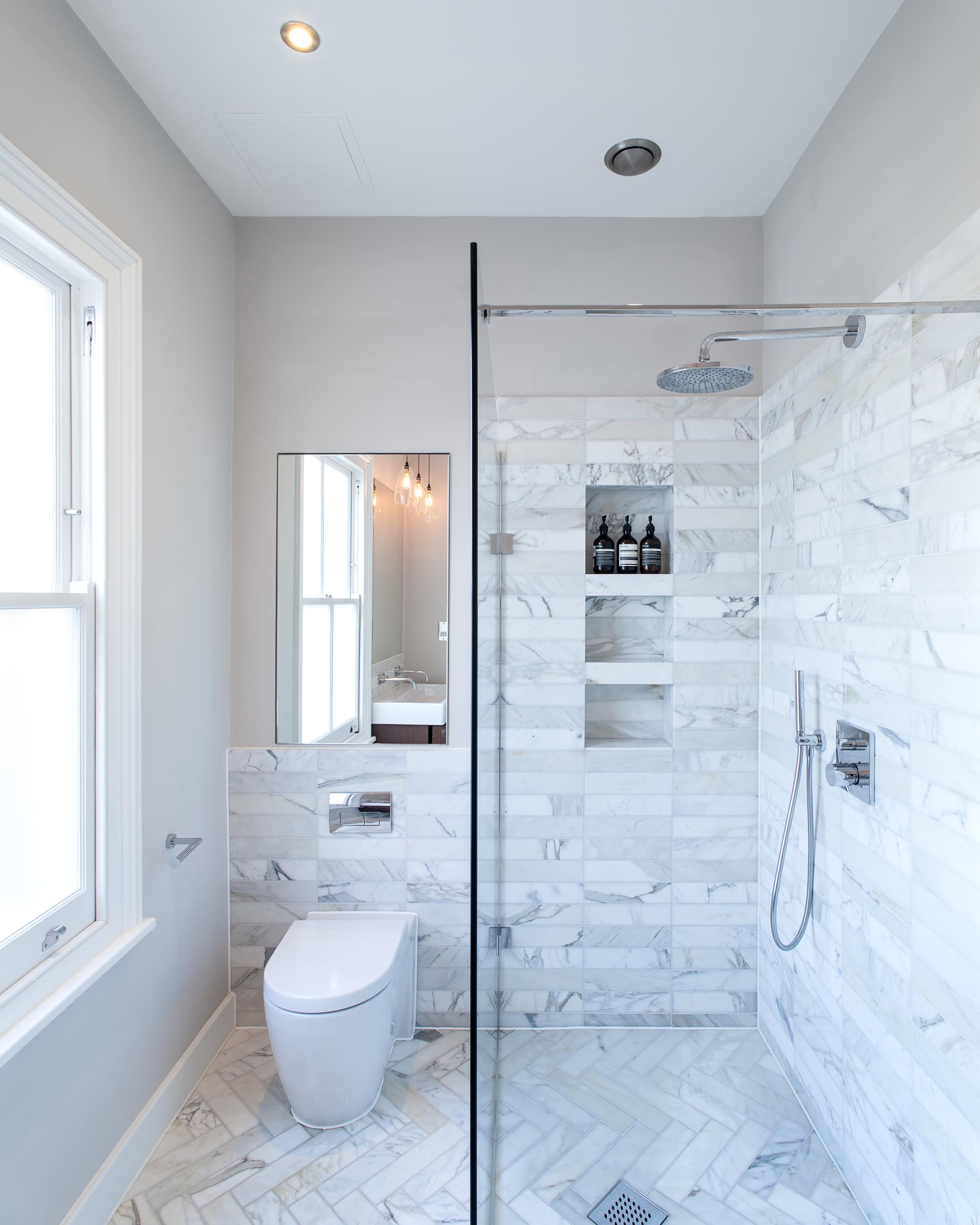 In this contemporary bathroom, gray stone tiles have been used on the floor and walls, while in the shower, there's a trio of built-in shower niches.