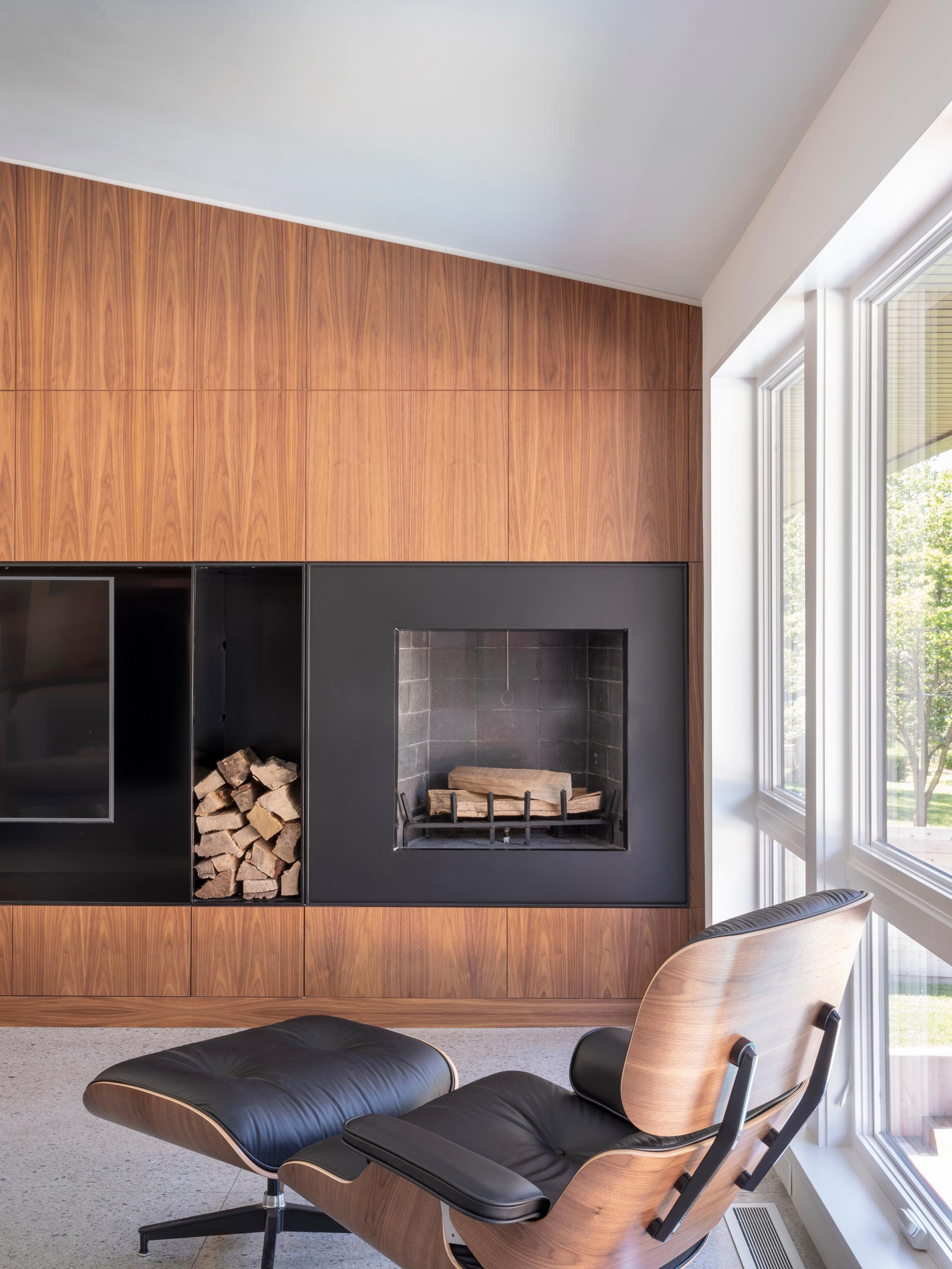 A modern living room with a wood accent wall that's split by the inclusion of black steel, which houses the television and fireplace.