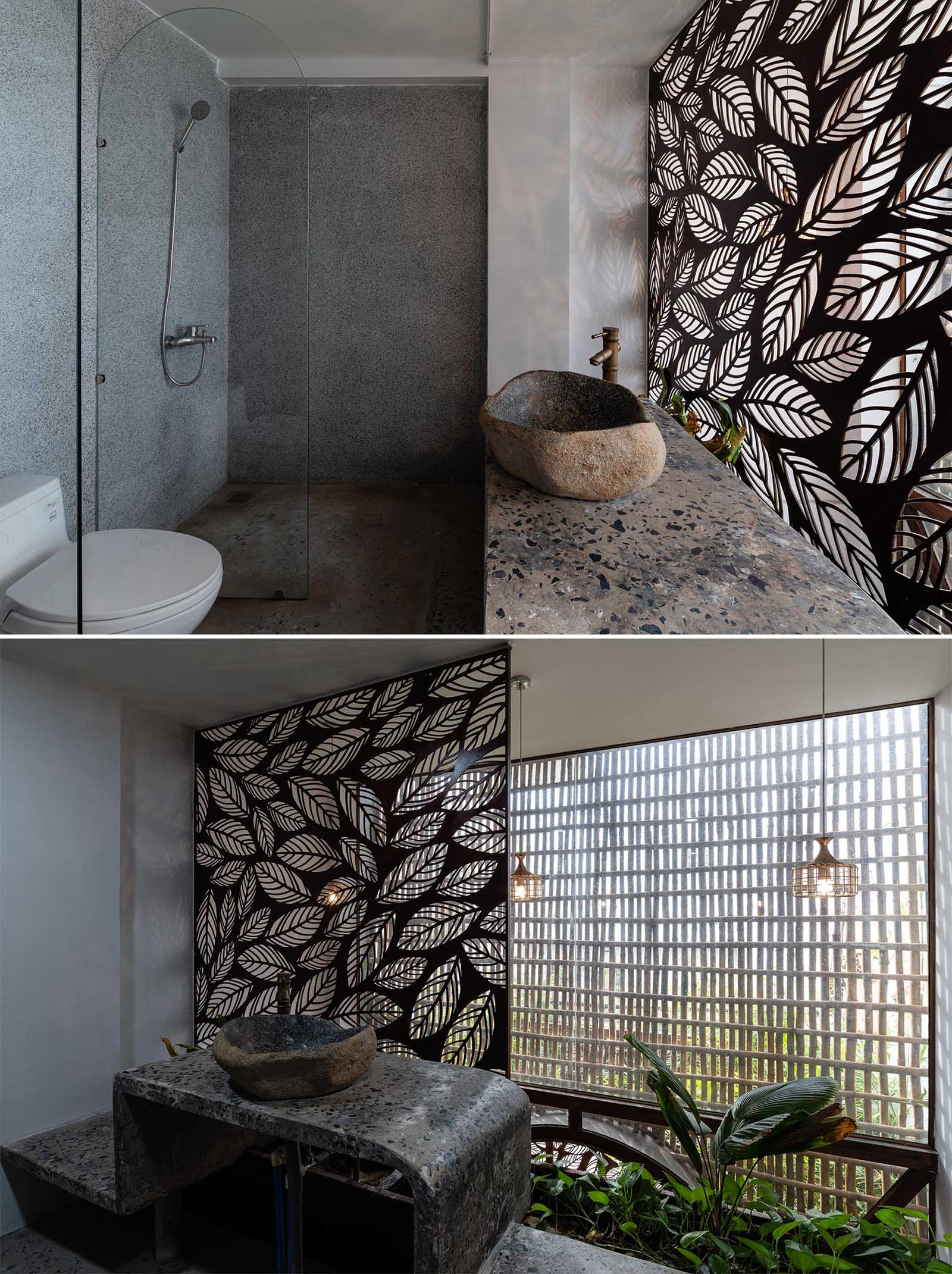 In this modern bathrooms, a decorative metal screen with a leaf motif has been used as a backdrop for vanity and as a way to highlight the doorway.