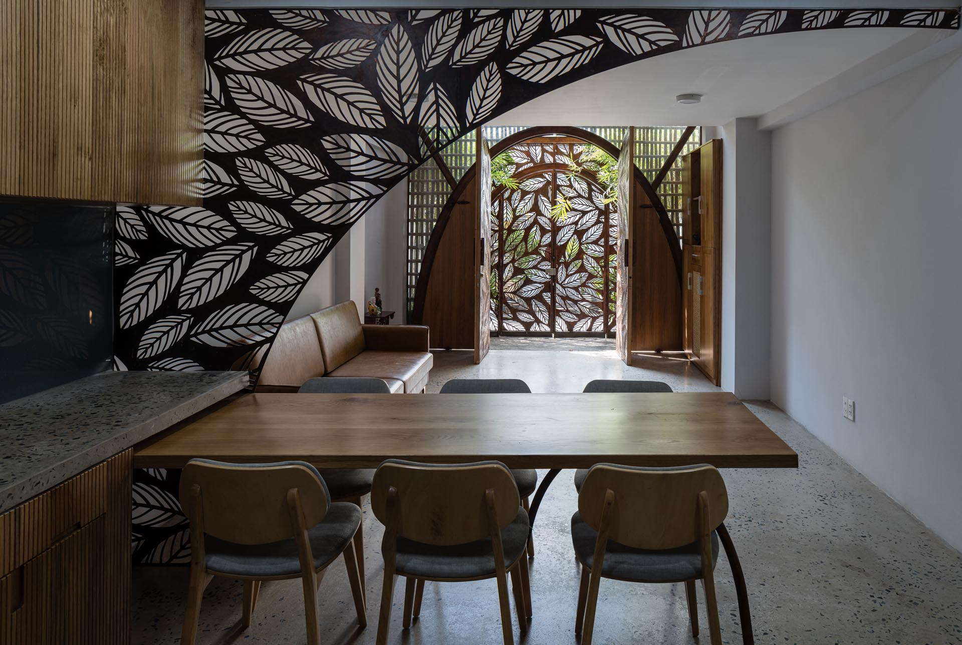 Stepping through to the interior of this modern house, there's a partial screen that acts as a divider between the living room and the dining area / kitchen.
