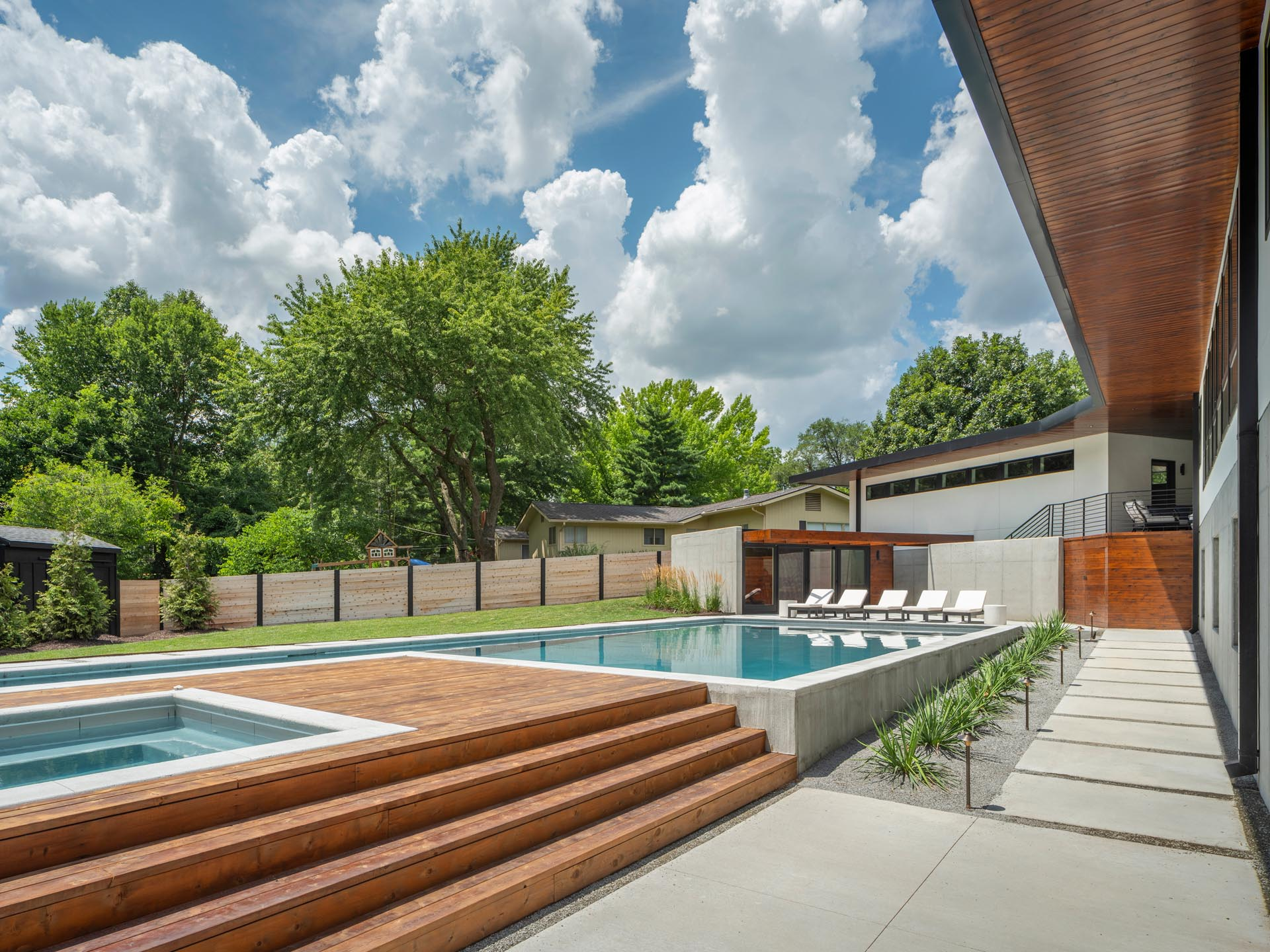 A mid-century modern inspired home with large landscaped yard, a swimming pool with a hot tub, a pool house, outdoor shower, and a deck.