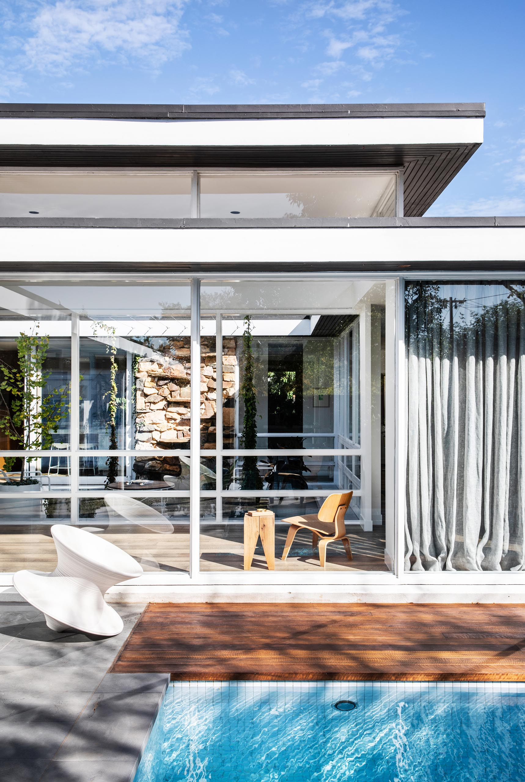 A mid century modern house with a swimming pool and floor-to-ceiling windows.