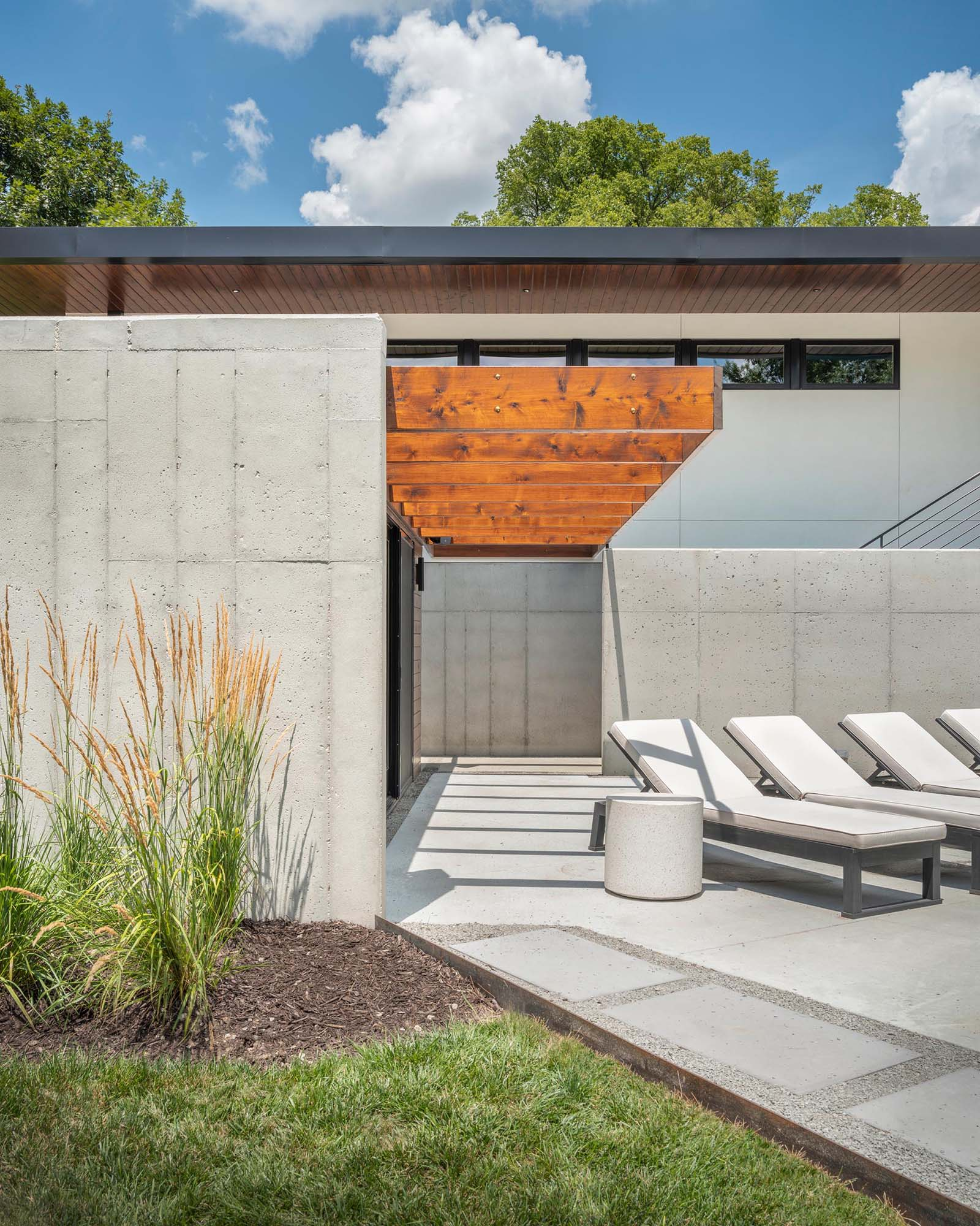 A home with exposed concrete that's accented by stained cedar.