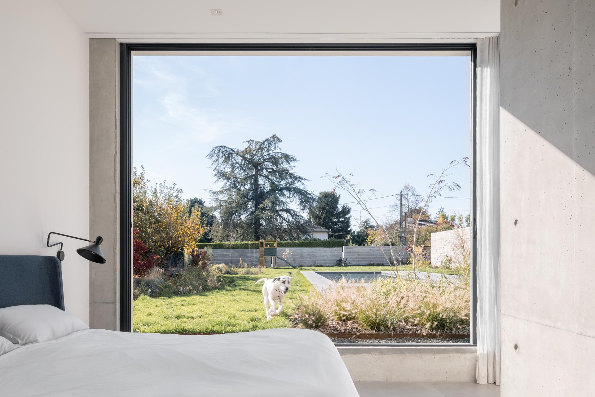 A modern bedroom with a large window that opens to the backyard.
