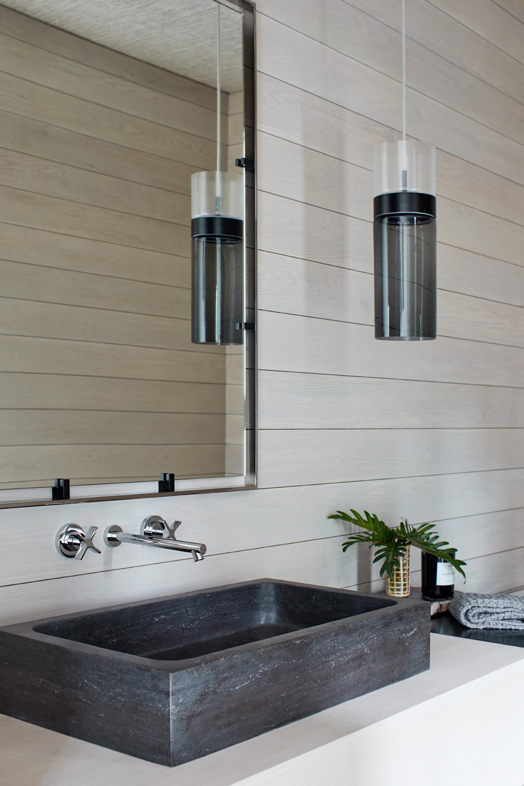 A modern bathroom with light wood walls that are contrasted by a black pendant light and sink.