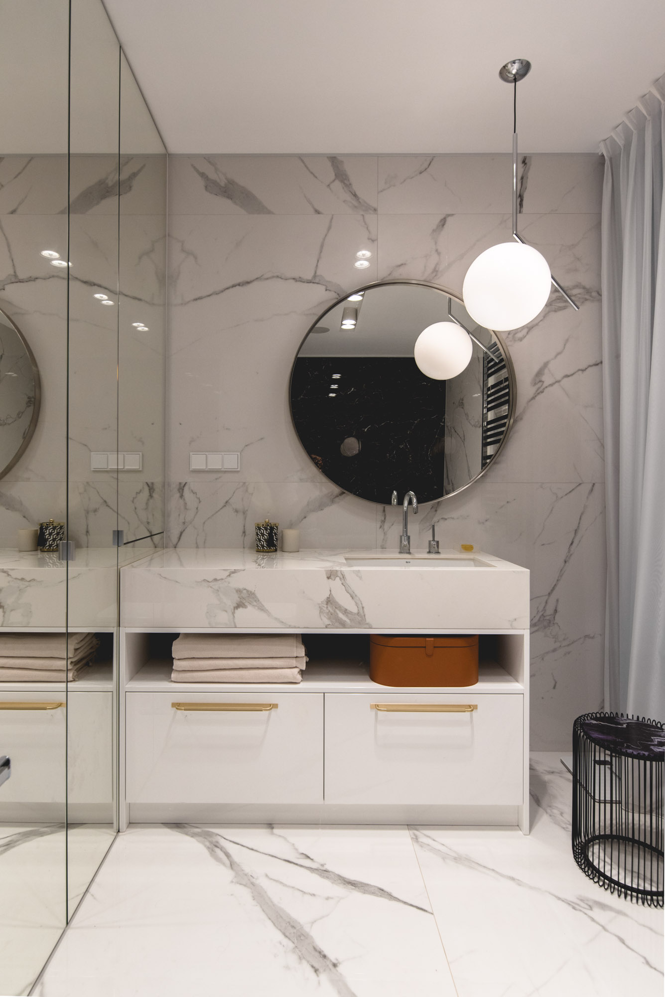 In this modern bathroom, stone covers the walls and the vanity, while the round mirror and pendant light add a curved element.