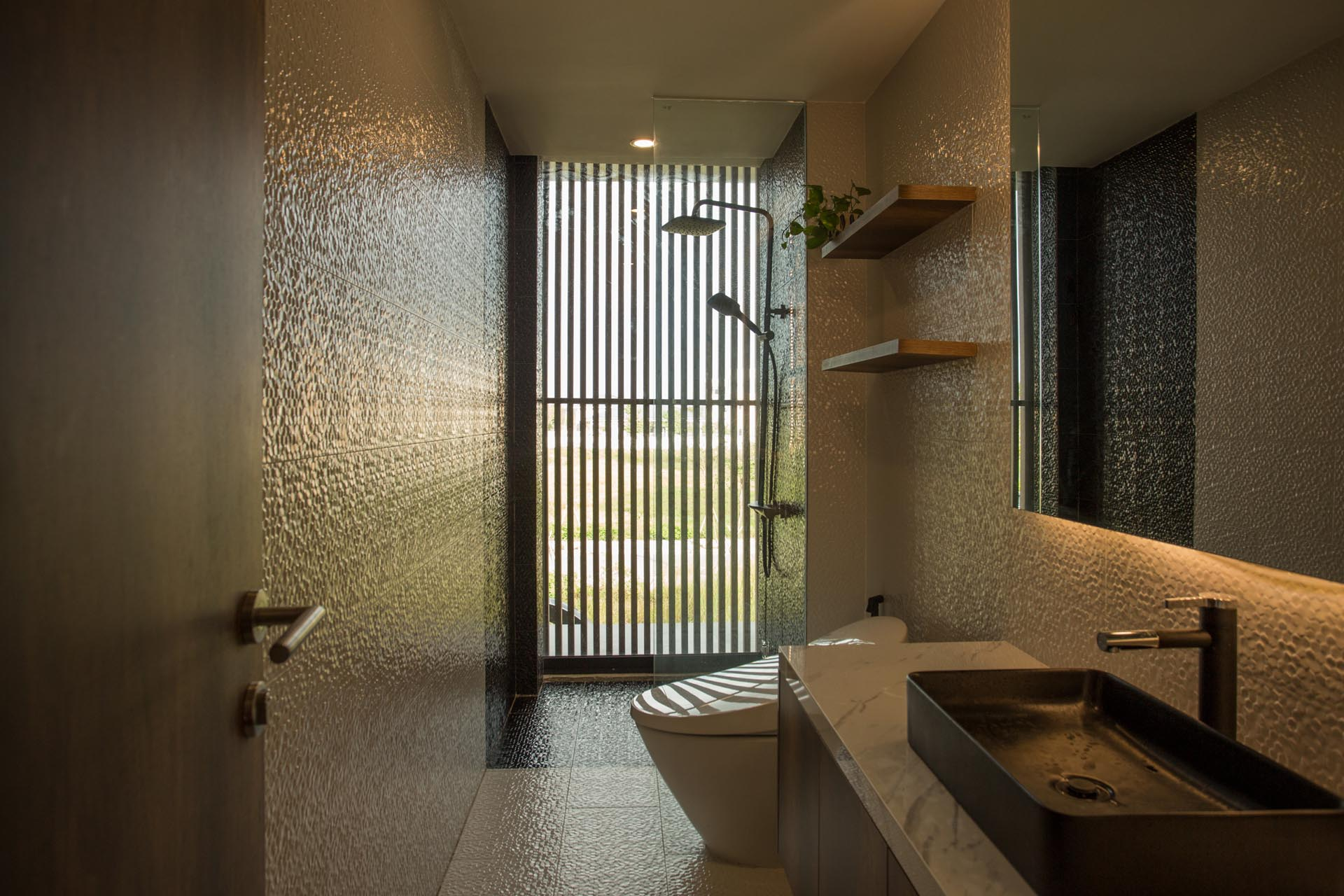 In a modern bathroom, textured tiles cover the walls and floor, while the shower is located by the window providing views of the outdoors.