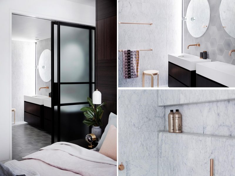 A modern master bathroom with marble walls, dual vanities, and hexagonal gray tiles.
