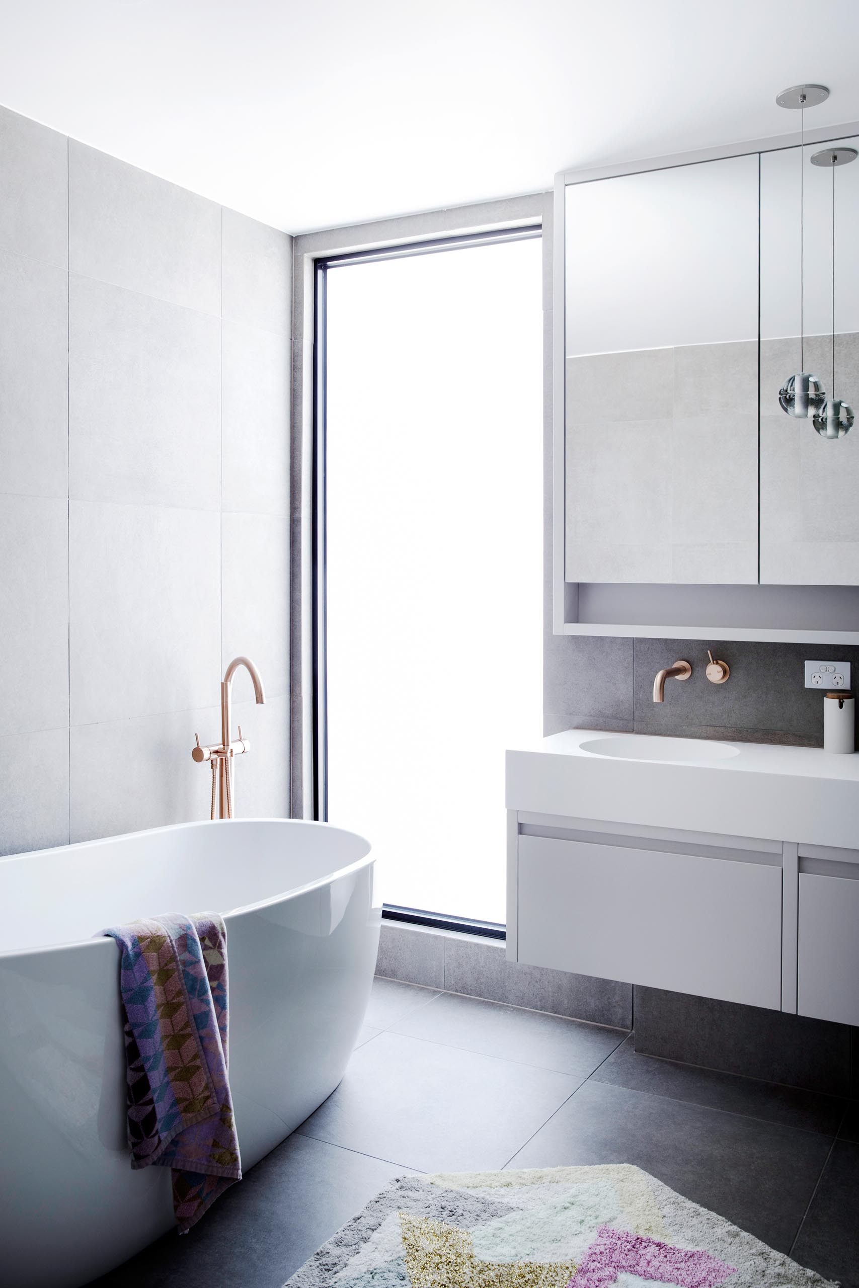 A modern bathroom with a large vertical window that floods the freestanding bathtub with natural light.