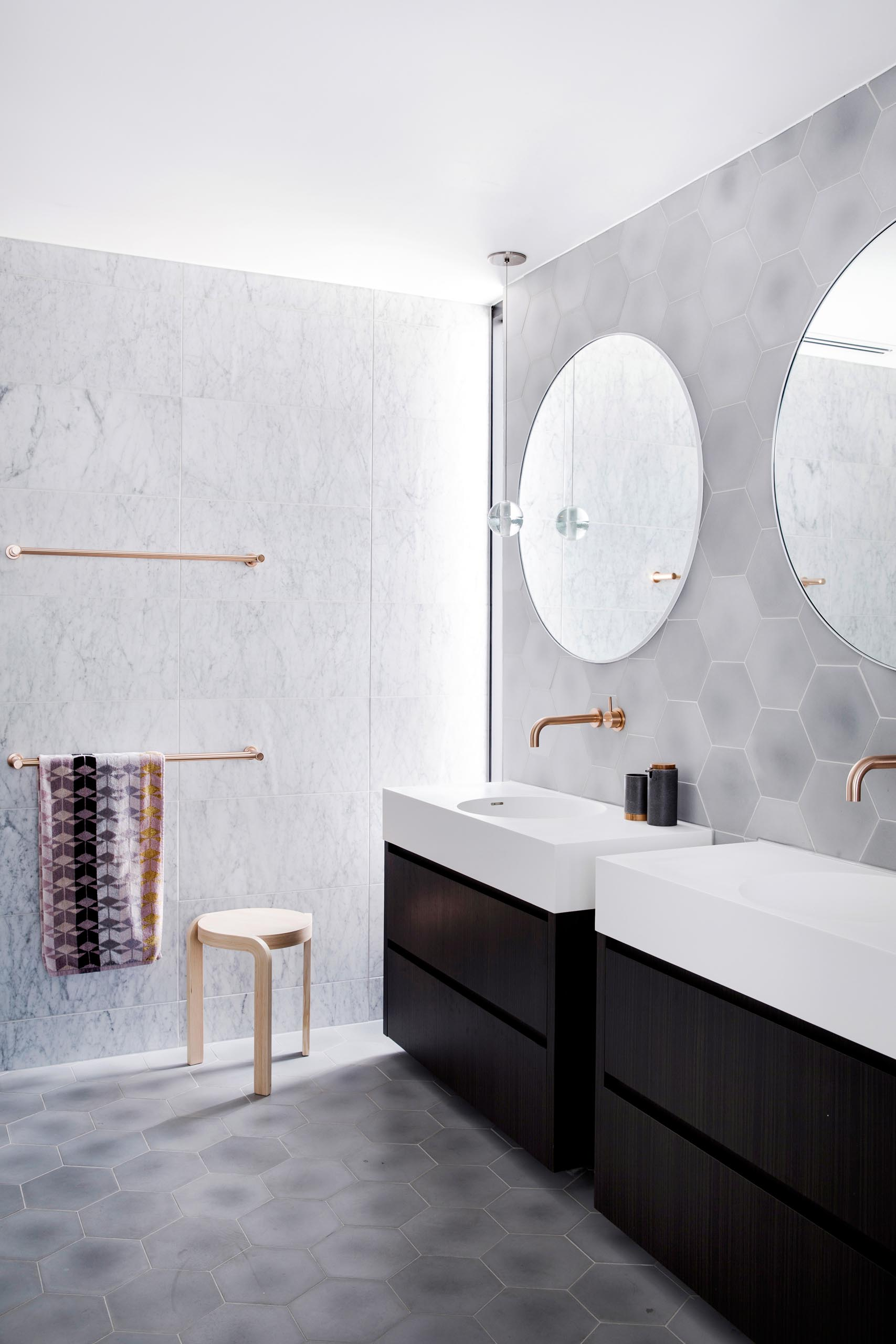 Stepping inside this master bathroom, natural light from the tall narrow window in the corner highlights the brushed rose gold towel bars mounted to the wall, that's covered with large format tiles.