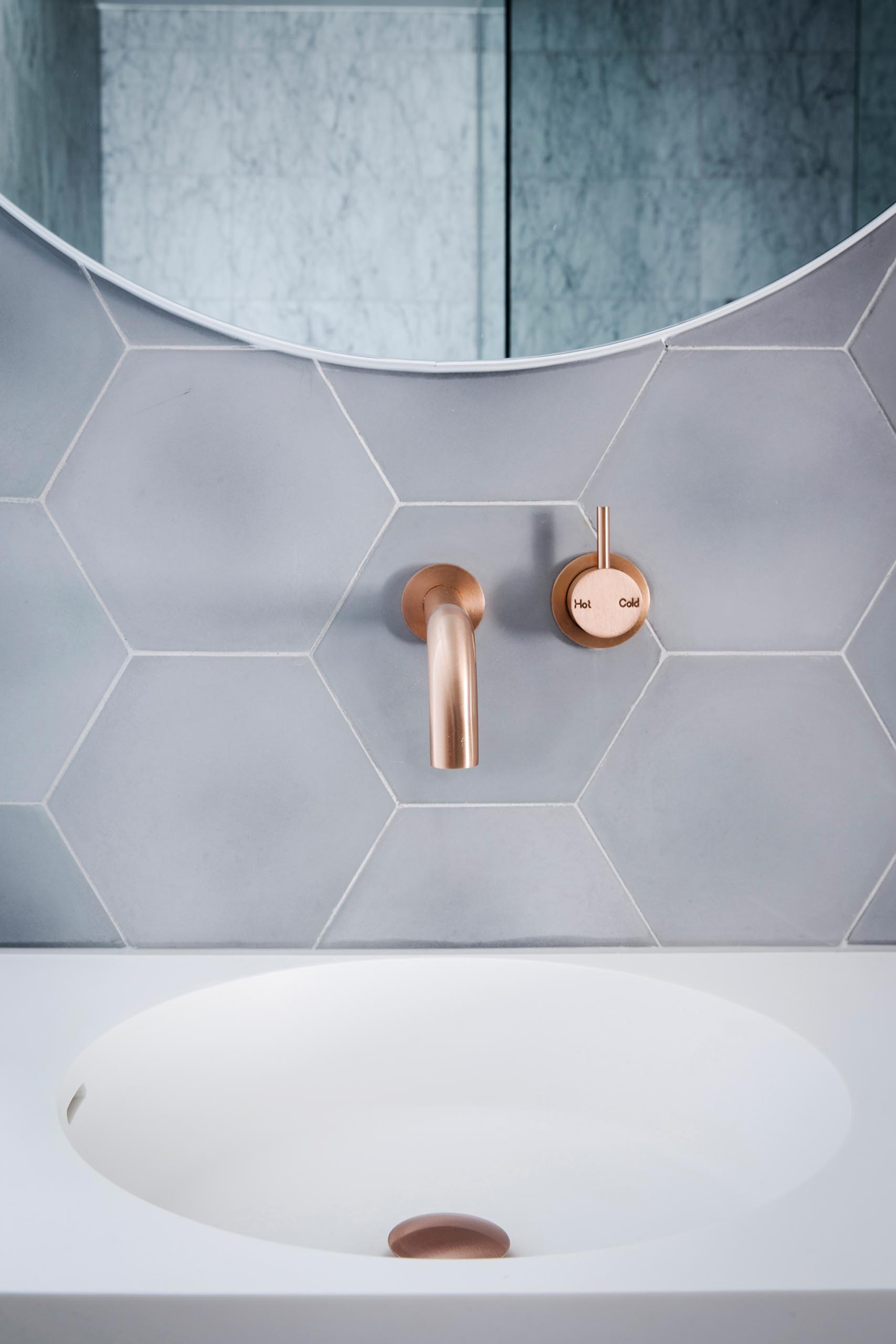 Hexagonal grey tiles with thin white grout provide a backdrop for the brushed rose gold faucet and round mirrors.