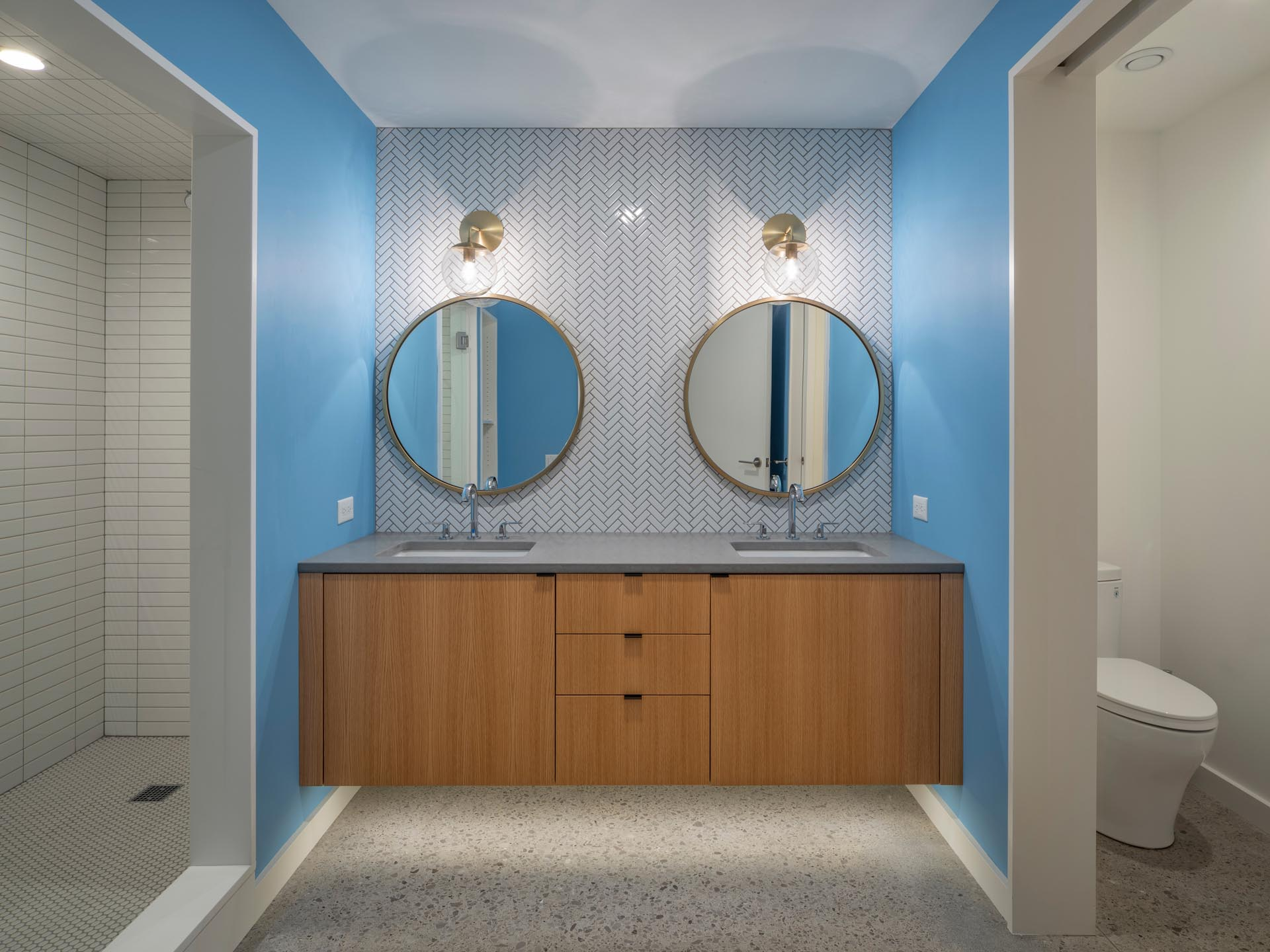 A modern bathroom with bright blue walls that add a pop of color, white a floating wood vanity has lighting underneath it, and above, there are two round mirrors with bronze frames that match the sconces.