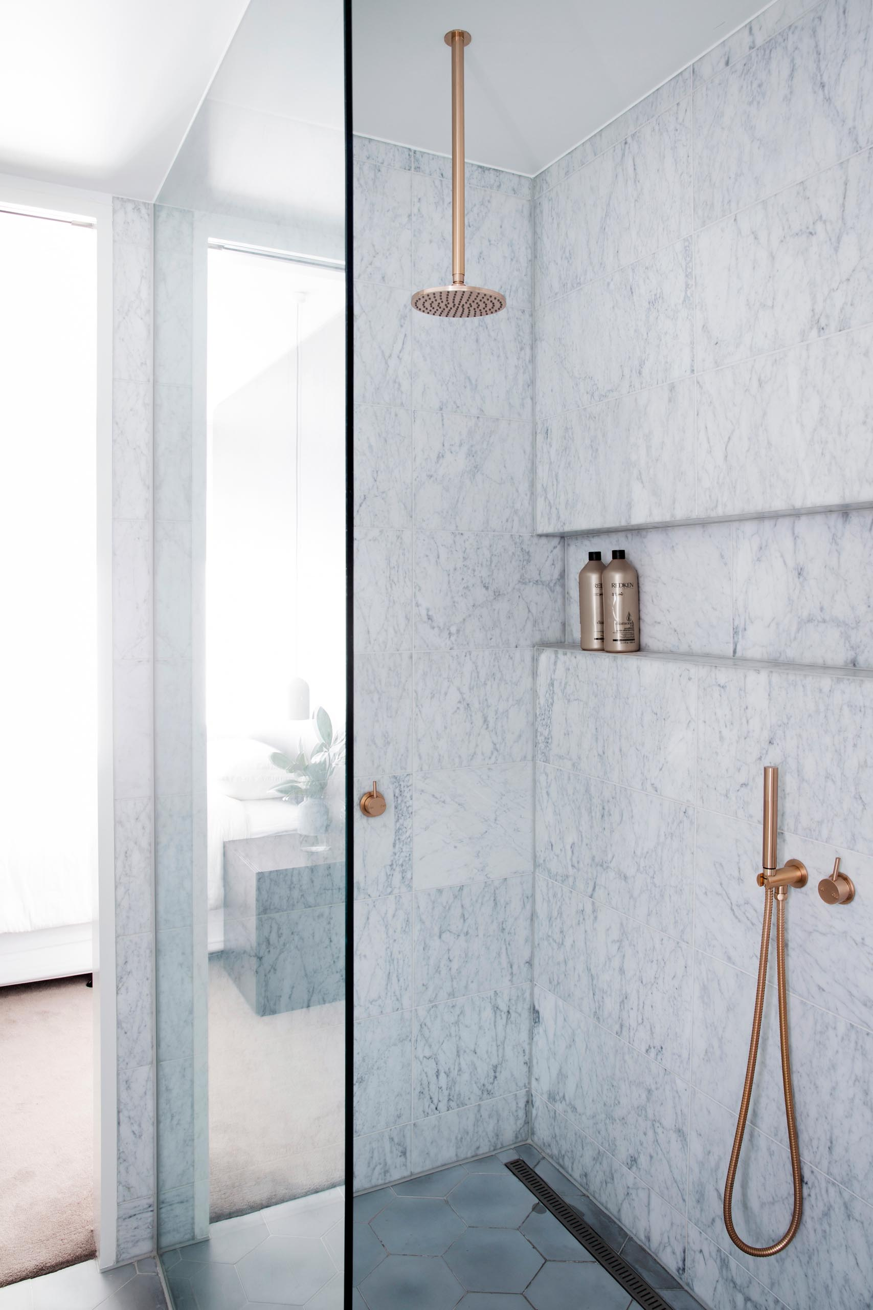 A modern gray marble shower with a rainfall shower head, brushed rose gold hardware, and a built-in shower niche.