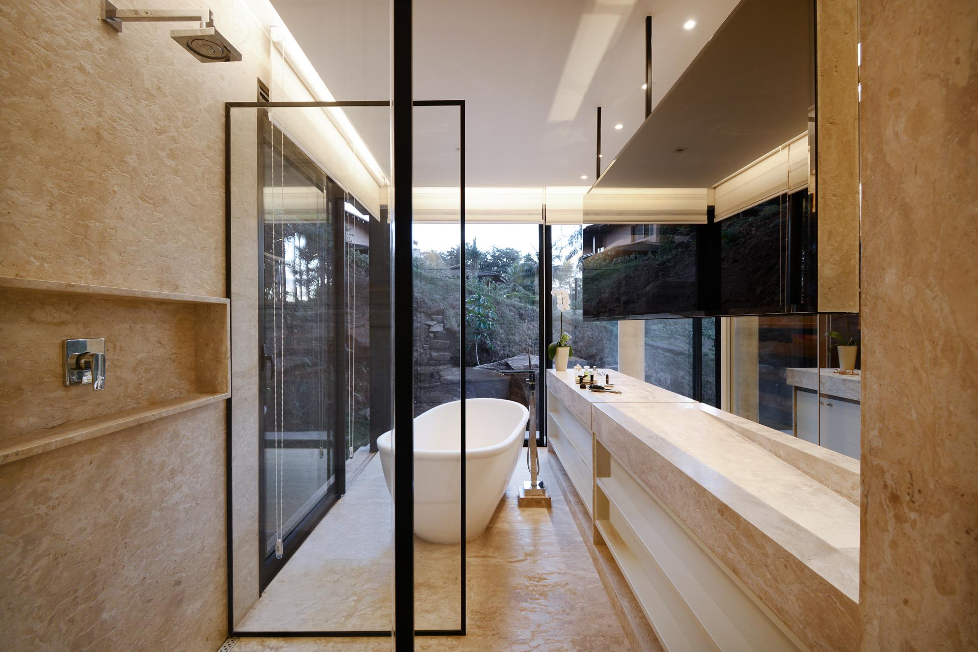 A modern bathroom with floor-to-ceiling windows that provide tree views for the freestanding bathtub.