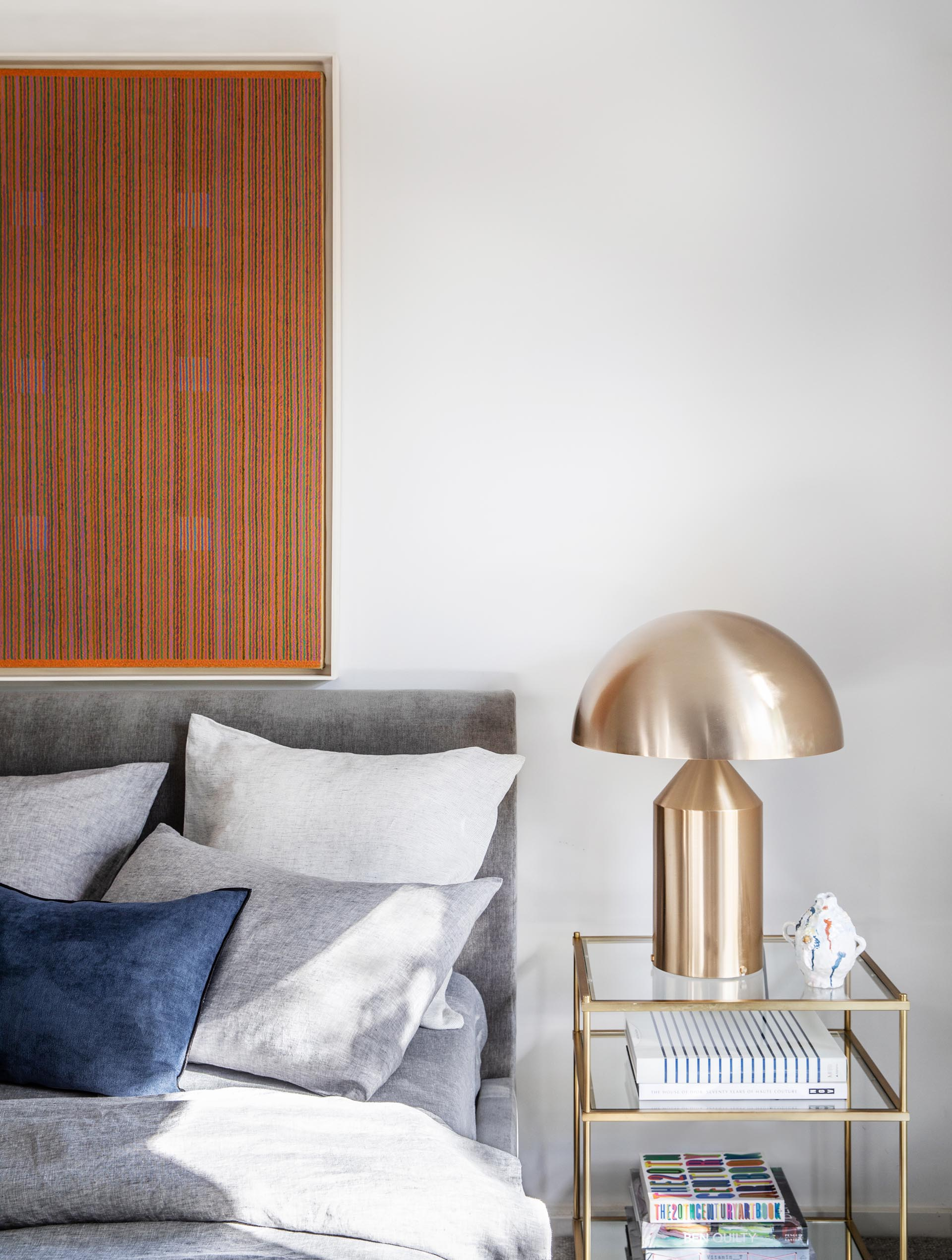 In this modern bedroom, an art piece and gray bedding adds color to the room, while the metallic accents add a touch of glamour.