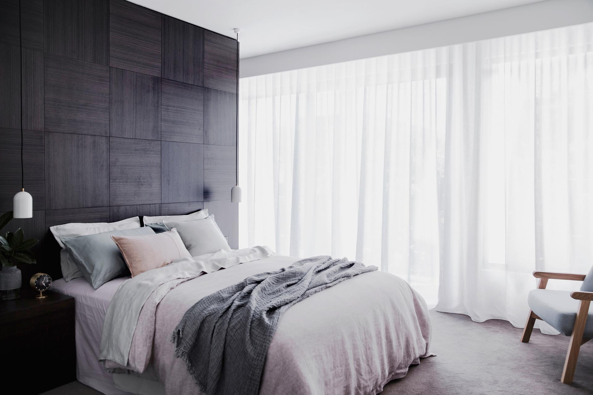 A master bedroom with a dark wood accent wall.