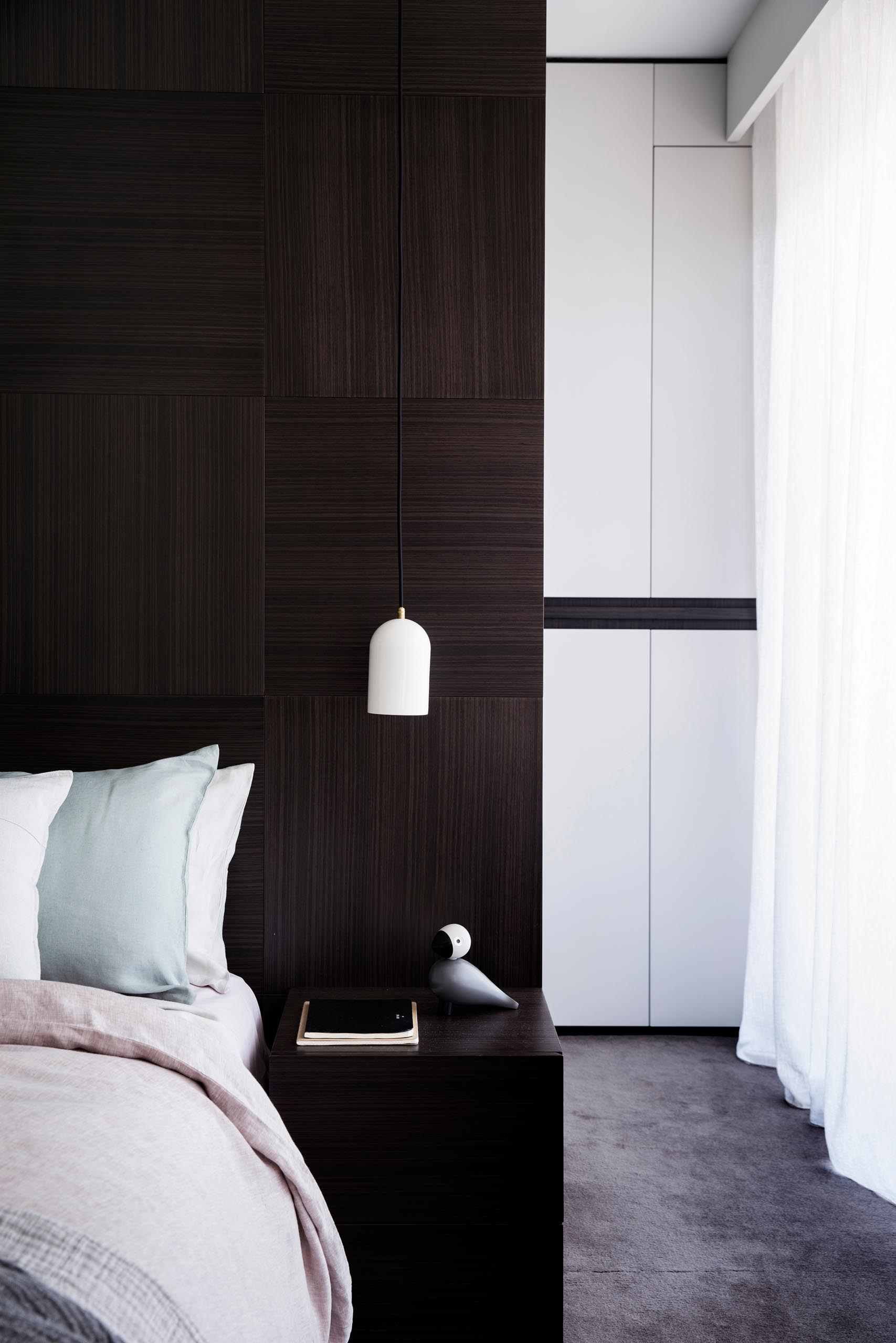 A modern master bedroom with a dark wood accent wall and a walk-through closet.